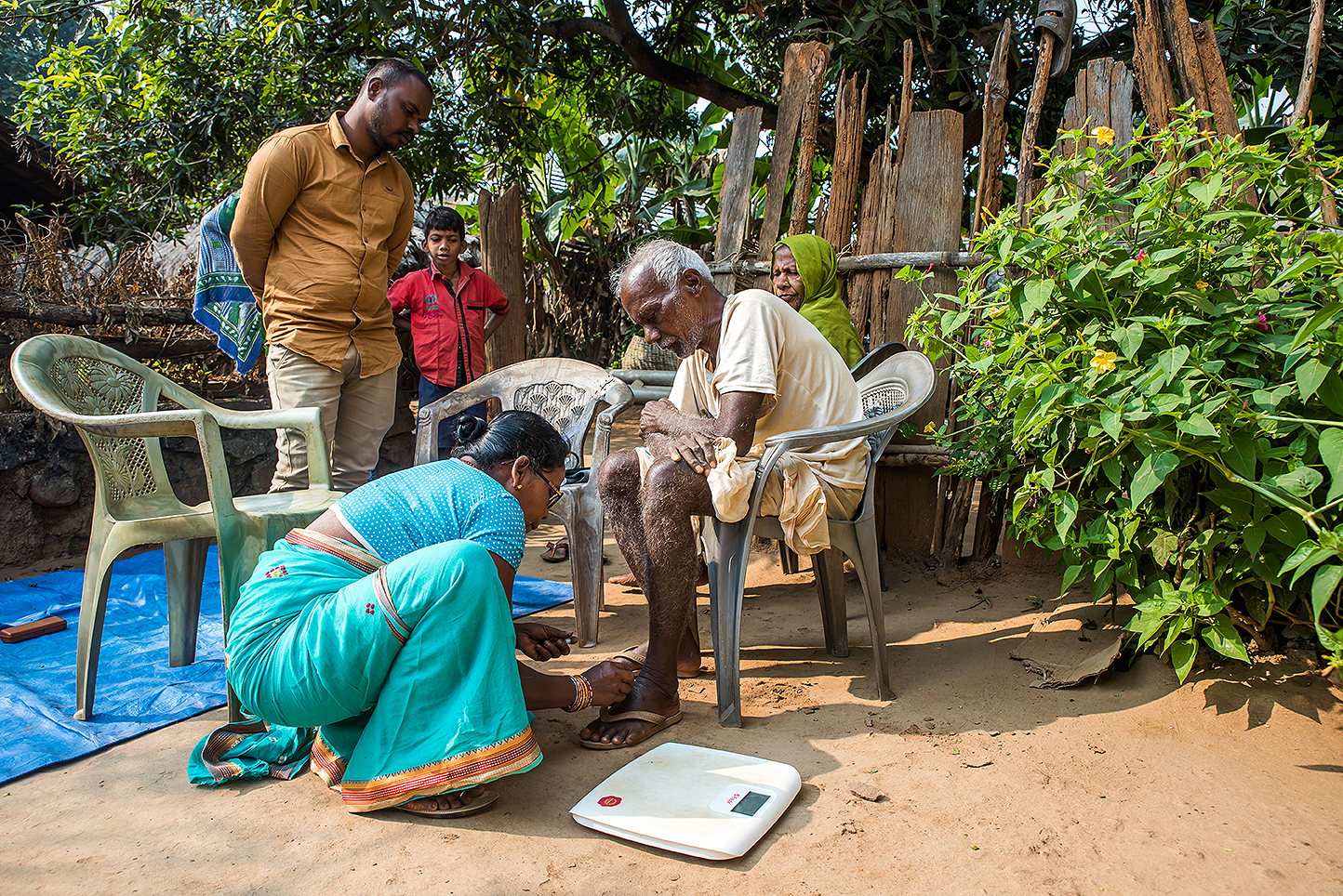 A community health worker trained by    Intelehealth    in rural Odisha evaluating a patient.
