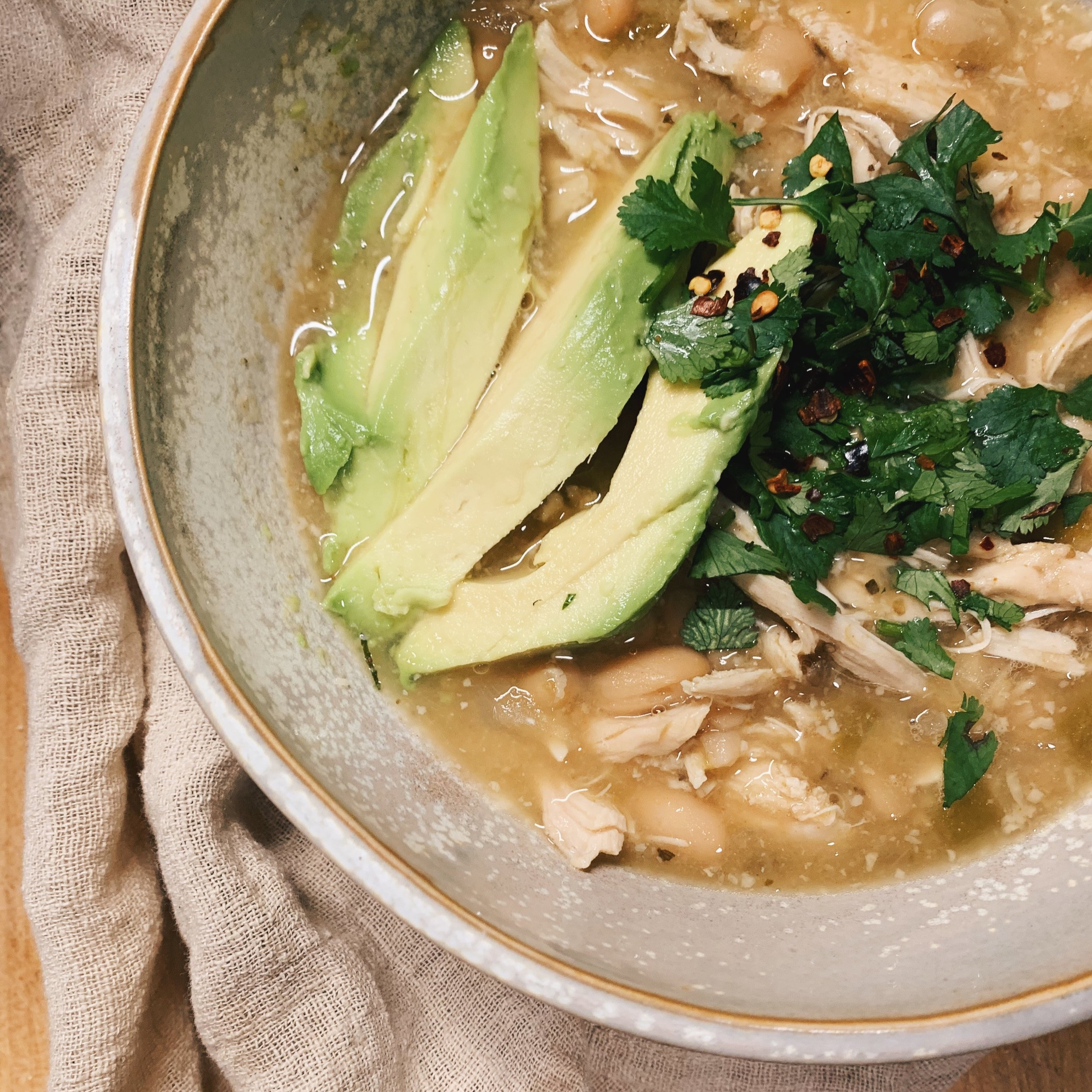 Crock Pot Green Chile Chicken   One of the EASIEST recipes to prepare! Little prep time and a short cook time well!  A yummy mix of Green Chile, garlic, cumin and topped with cilantro and avocado, duh!! Enjoy!  Minor adjustments: 3 cups of broth instead of 4, blended 1/3 (ish) for more thickness!   Recipe    here!