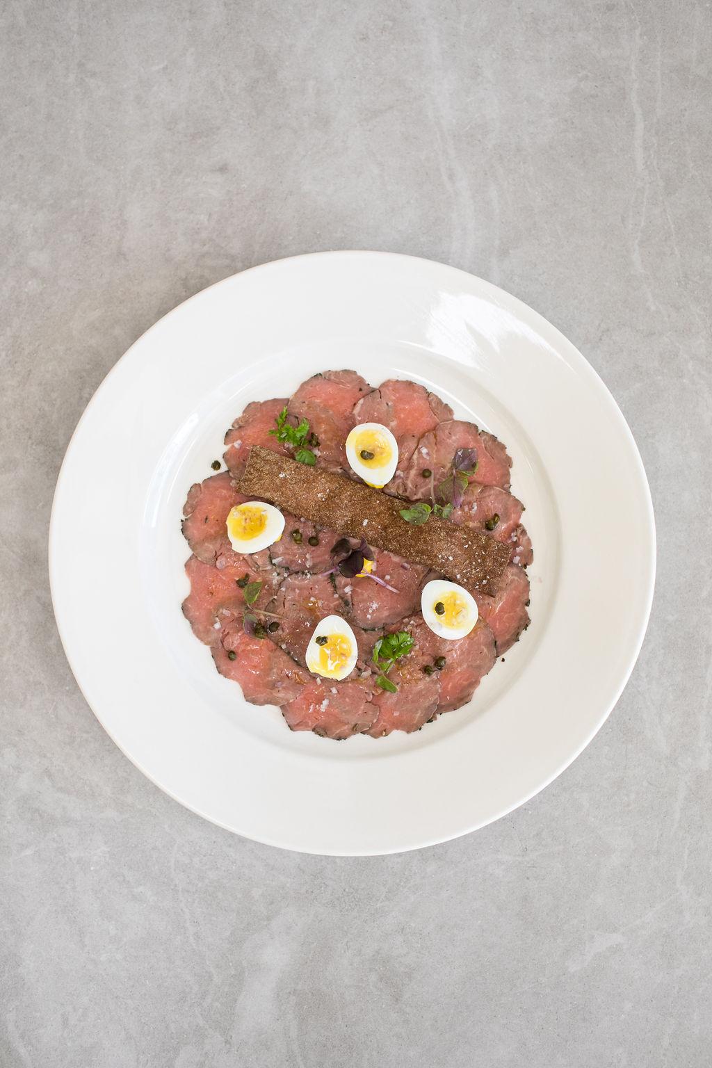 E- Seared beef carpaccio, shallots, quail egg, crispy capers, rye crisp and saffron aioli (df).jpg