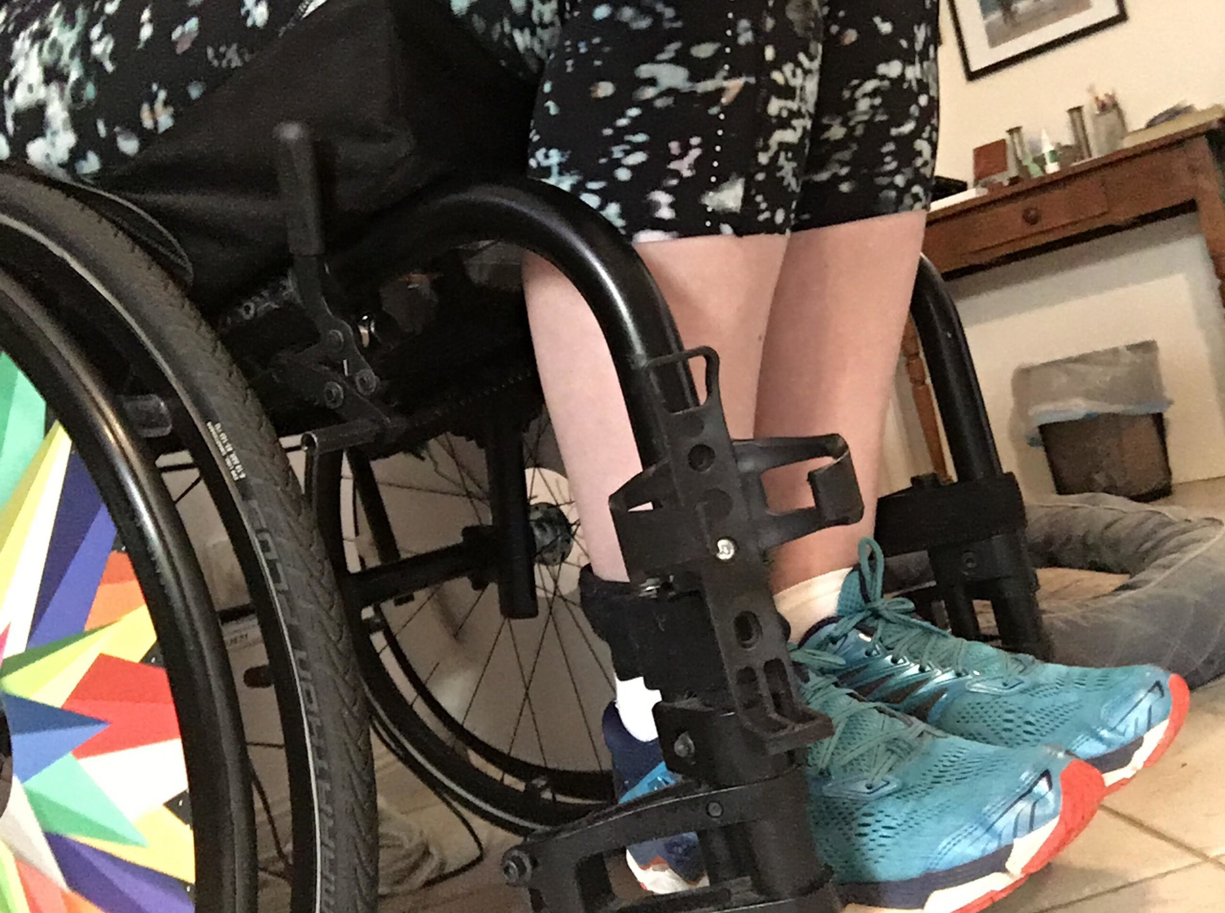 [Image description: A photograph of my legs in a wheelchair. The wheelchair frame is only partially visible, but you can see it is black, with rainbow spoke guards. I am wearing blue runners and black three-quarter-length tights with blue spots.]