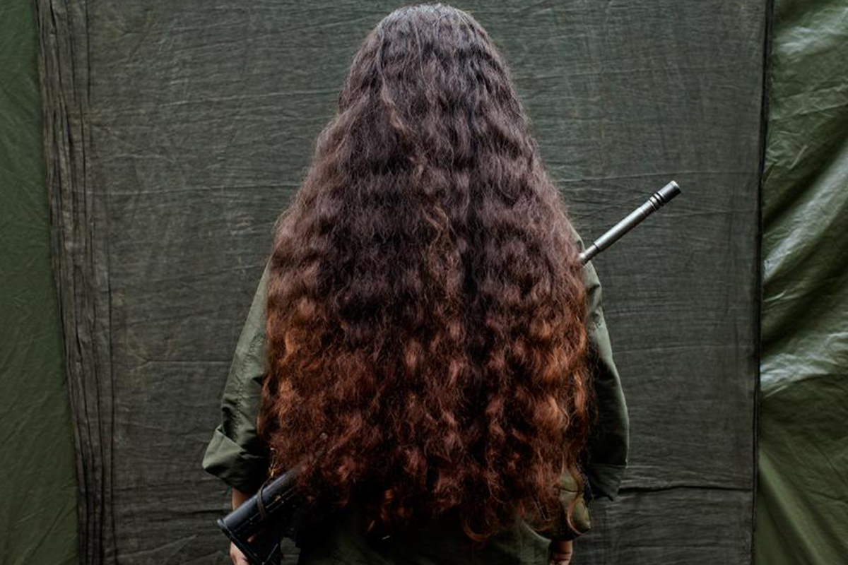 A shot from a woman's back with her hair covering a gun from Rape as a Weapon of War in the DRC episode.