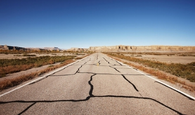 cracked-desert-road-leading-into-the-distance-gary-yeowell.jpg