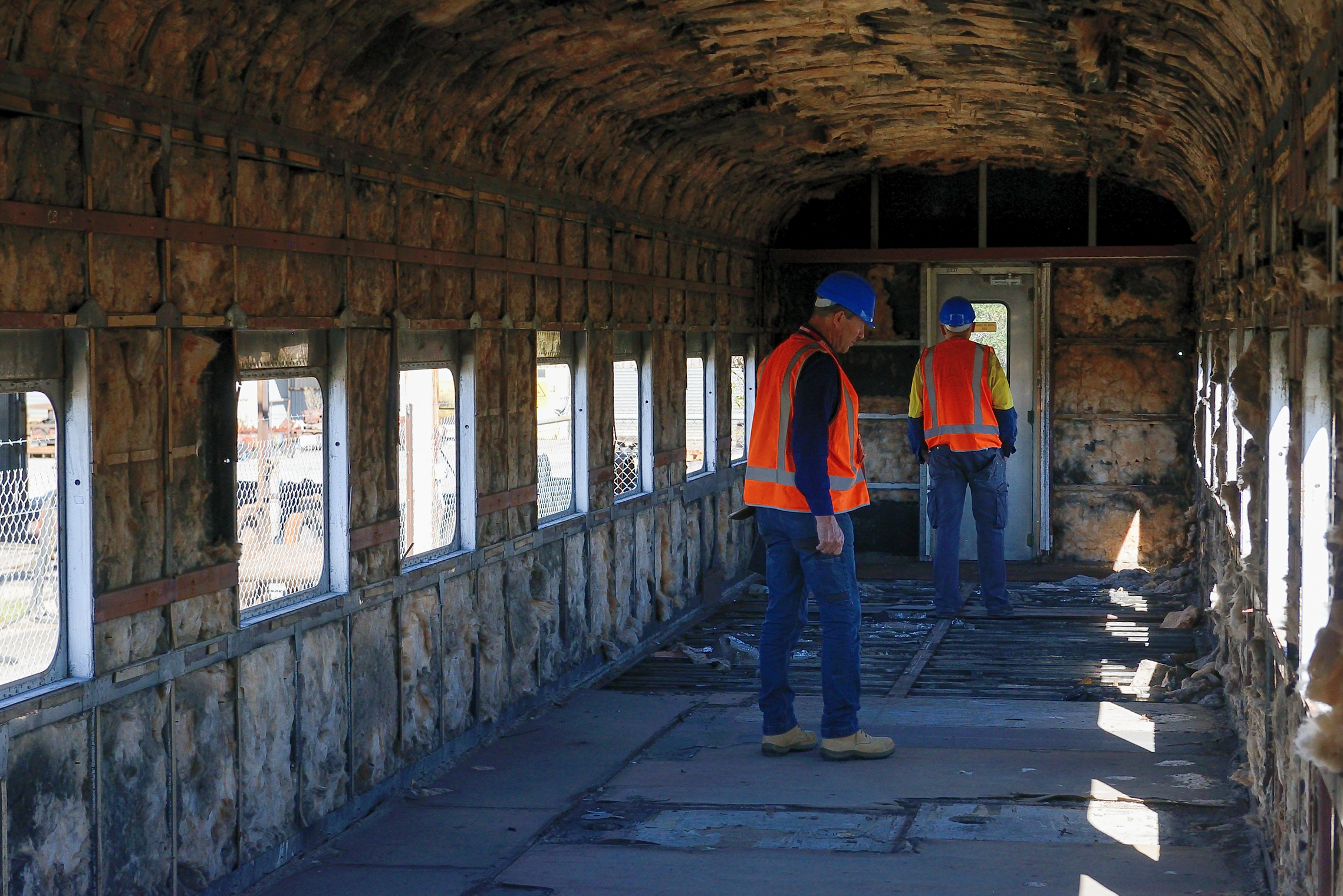 Jeff Jennings and Iain Atkin inspecting the inside of the stripped carriage at Downer's Newport Workshop.