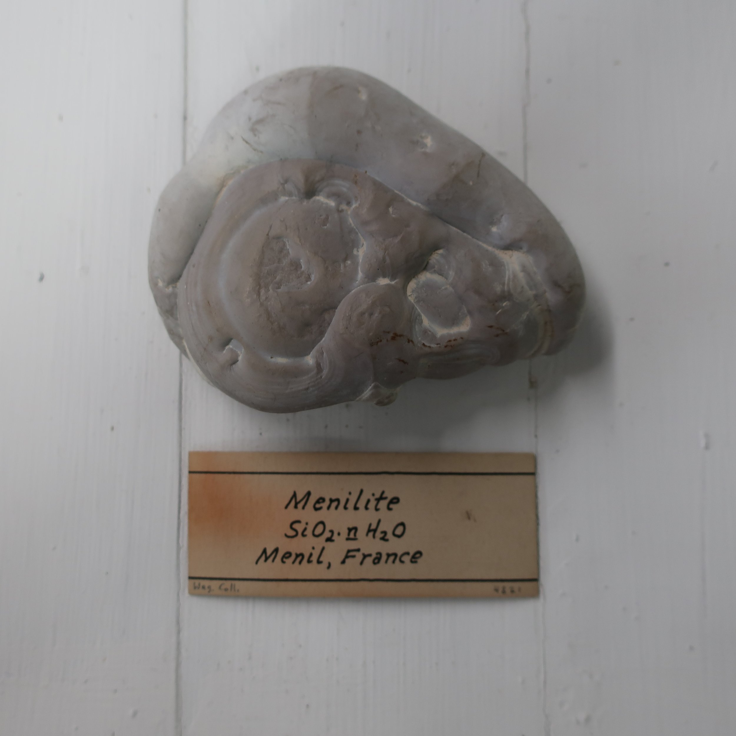 """Menelite  is a variety of semiopal occuring in compact reniform masses of a brown colour, structure slaty, found in beds of adhesive state at Menil-montant near Paris. It contains 85 silica, 1 alumina, and 11 water."""