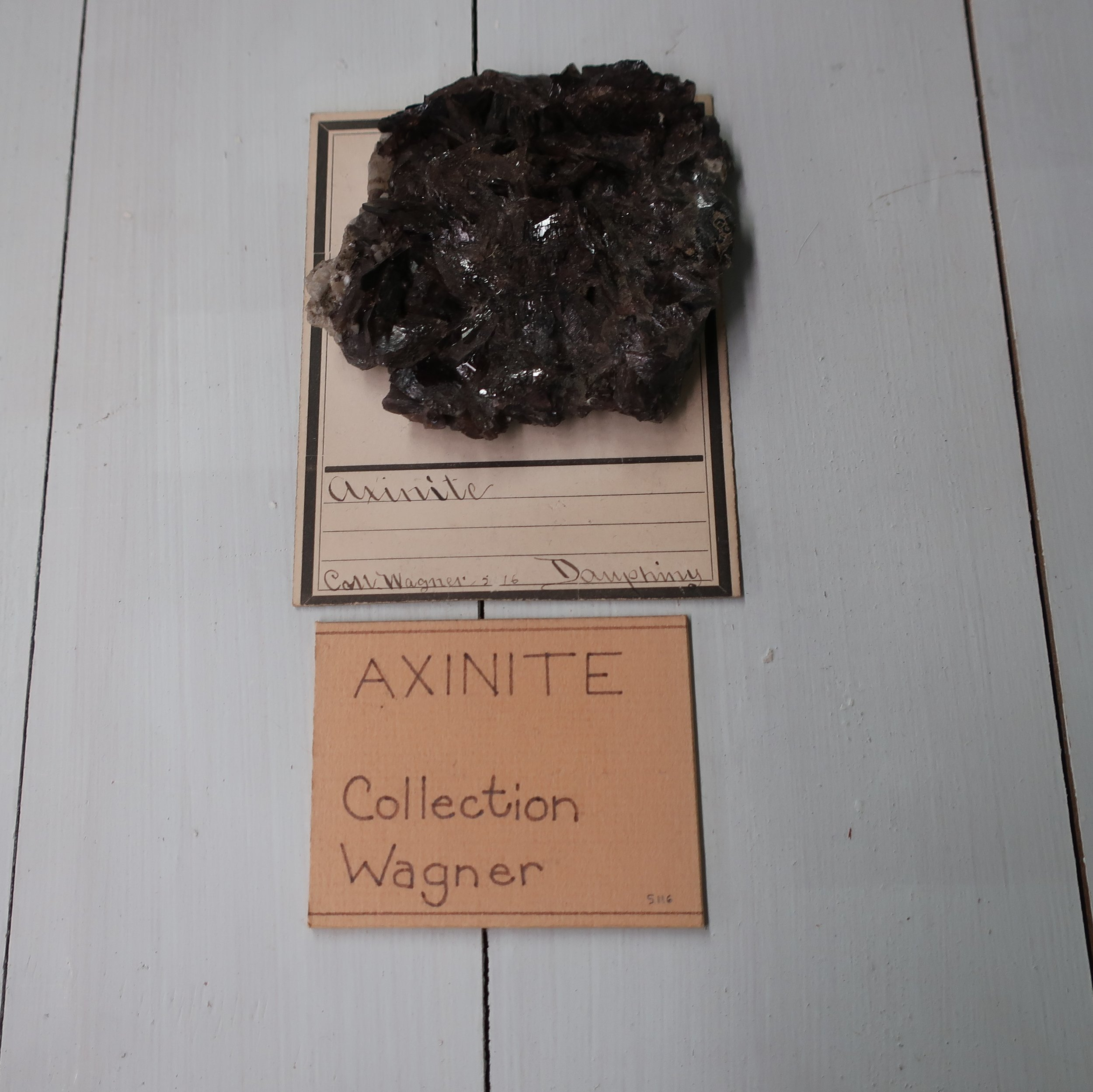 """ Axinite  contains Silica 50, Alumina 16, Lime 17, Iron 9 Manganeese 5. Sp. Gr. 3.27. This mineral rarely occurs massive, more frequently in flat, oblique rhomboidal prisms, whose edges are remarkable sharp. Common colour violet, or clove brown, also yellow, and green, from an admixture of Chlorite. Externally the crystals are remarkably brilliant becomes electric by exposure to heat. BB it fuses readily into a green glass. It is not acted on by acid. It occurs in Saxony, and the Pyrenees, the finest crystals are found in Dauphiné in France, but one locality has been found in the U States, at Phippsburg Maine."""