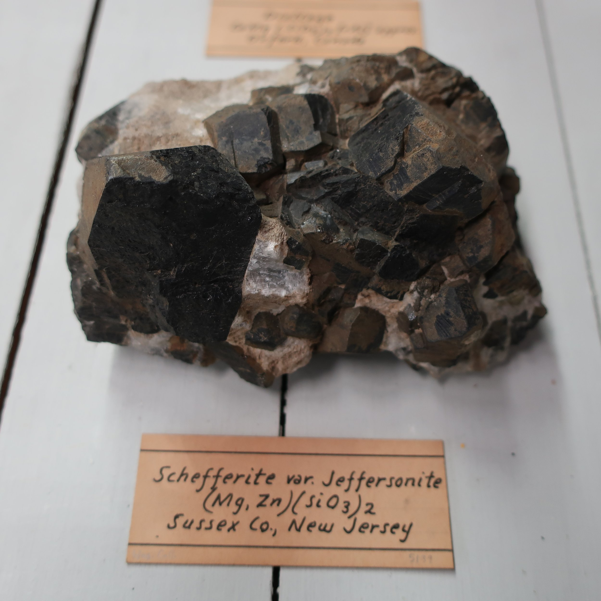 """Jeffersonite  was discovered by Msrs Keating, and Vanuxem of Phil""a from its chemical composition and other characters, they came to the conclusion it was a new species. Dr. Troost instituted a careful comparison between this mineral, and pyroxene, as to its crystaline forms, and has shewn, that its crystals, correspond precisely with the latter, and it is now classed as a variety of Pyroxene, in the systems. It contains Silica 56. Lime 15. Manganeese 13. Iron 10. Sp. Gr. 3.5. It is found in large foliated masses, sometimes a foot in length, and in groups of large, and well defined crystals, from 2 to 6 in. in diameter, usually of a dark olive green colour, passing to brown. It occurs with Franklinite & Garnet at Franklin Sussex Coy N Jersey."""