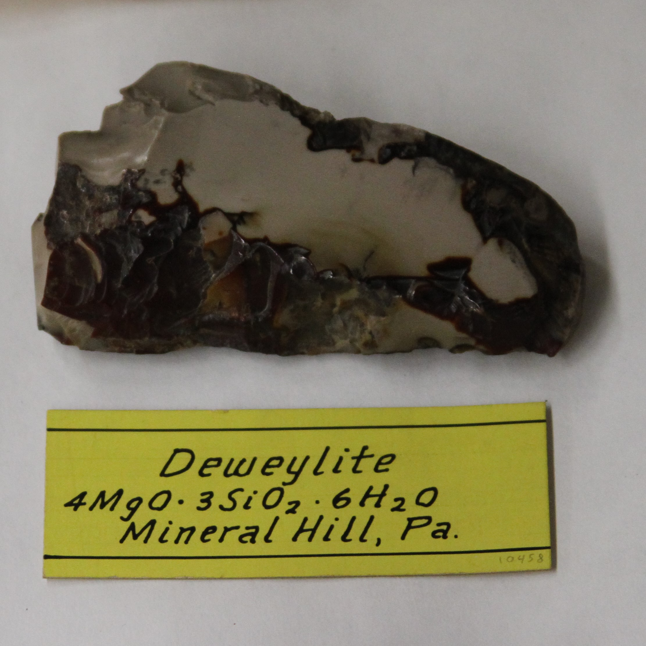 """Deweylite [ is a variety of Serpentine] found in seams and irregular veins in Middlefield, Massachusetts. It contains Magnesia 40, Silica 40, Water 20, Sp Gr 2.3. It is yellowish and greenish white, lustre is vitrious, inclining to resenous, easily frangible when emersed in water."""