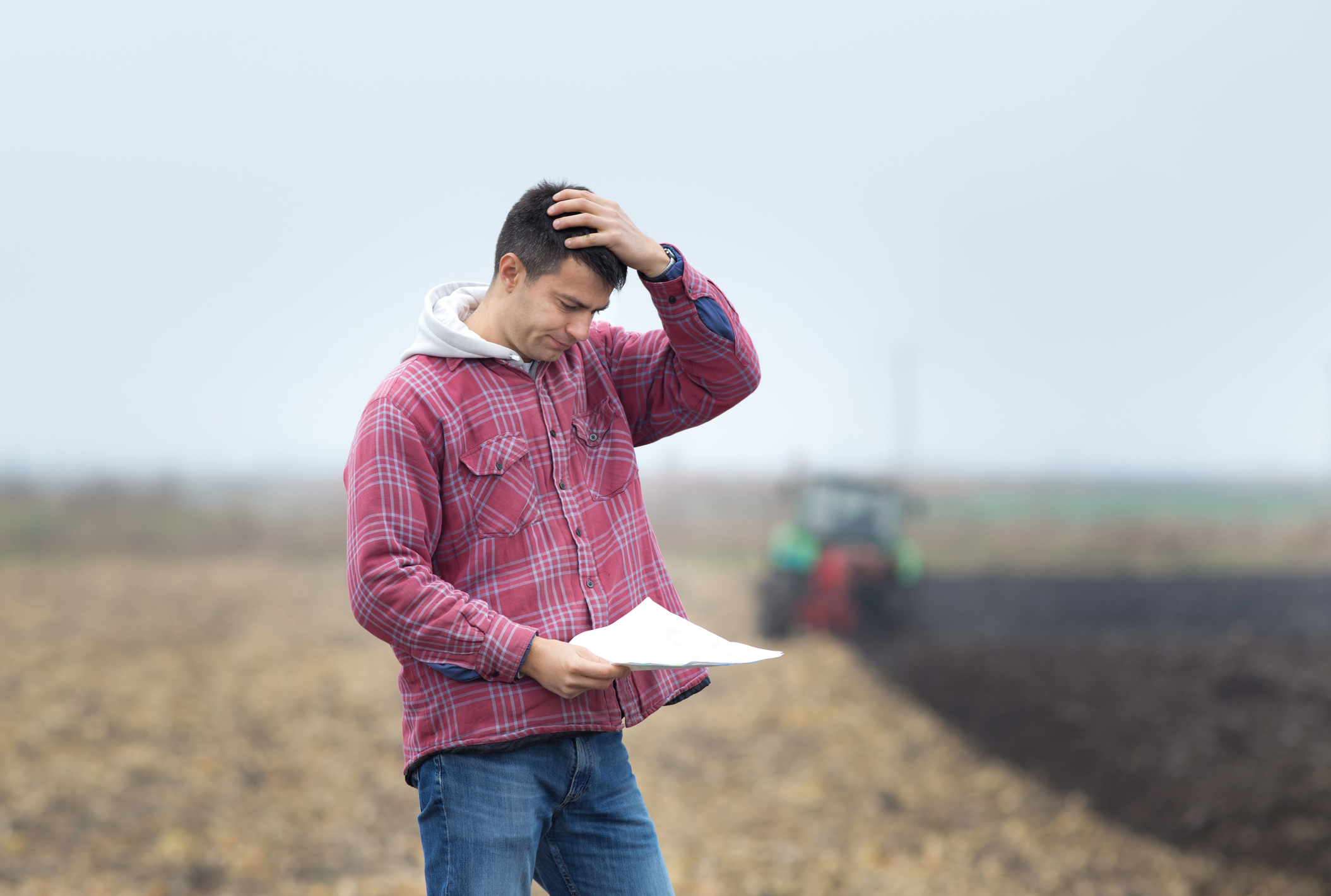 A man in a farm field holding his head while looking at paperwork