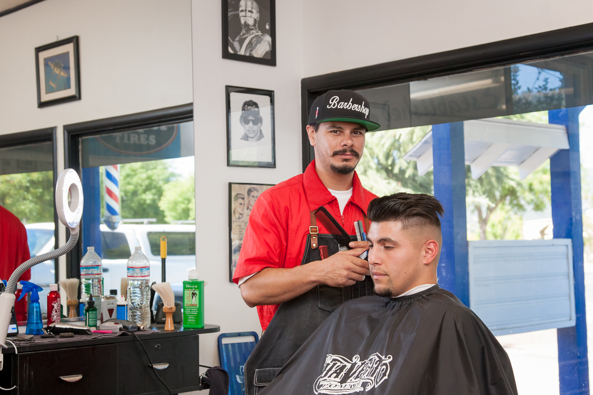 Marc Saavedra cuts a clients hair at his business, Airport Barbershop, in Ukiah, CA.
