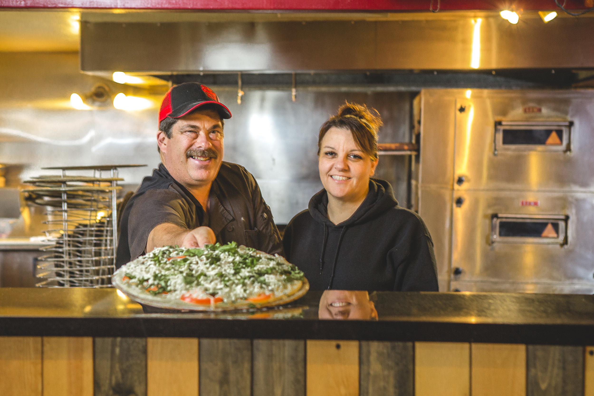 Owners Matt and Stephanie Dunken hand a pizza over the counter at Slam Dunk Pizza in Ukiah, CA.