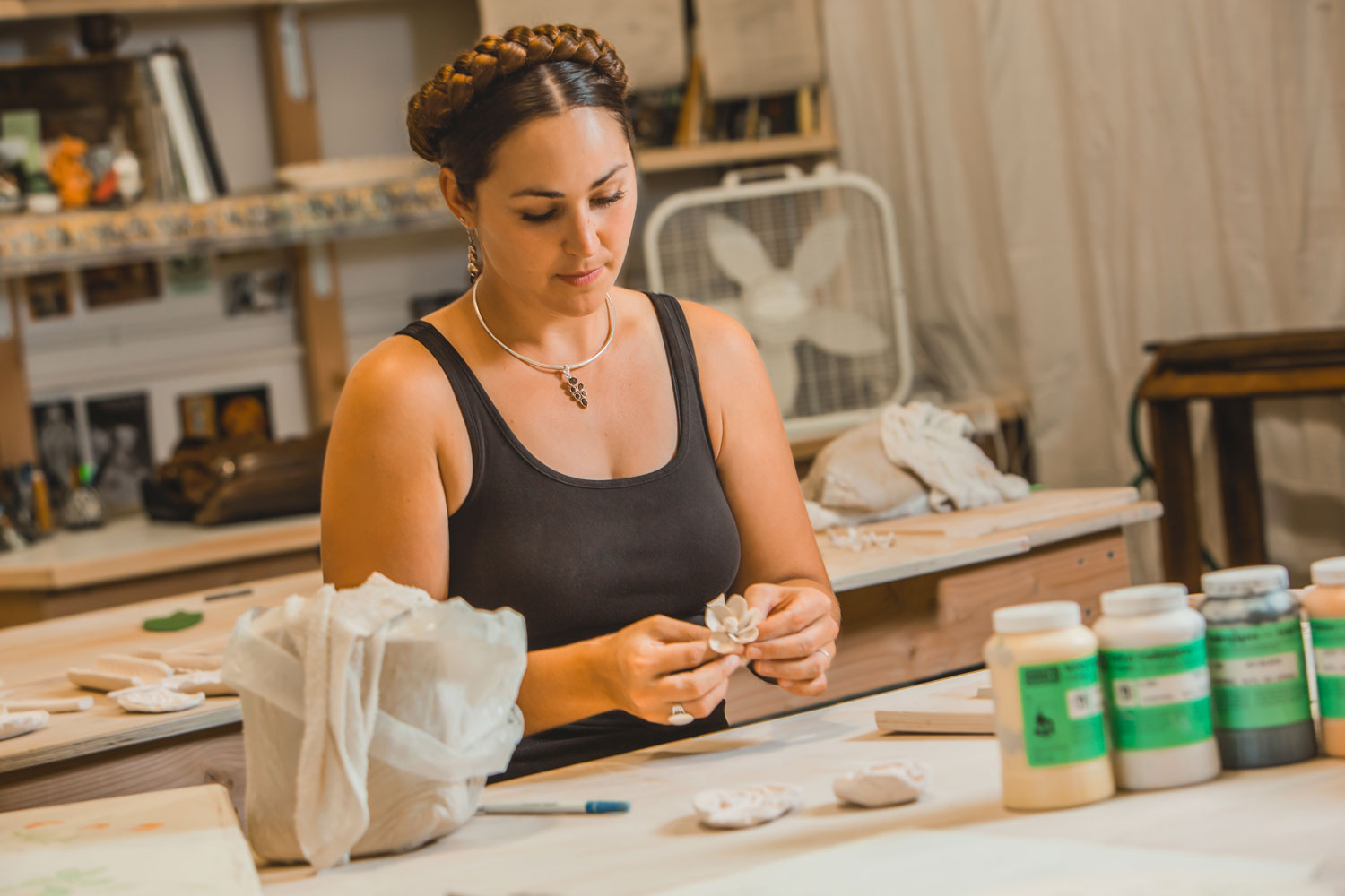Katharine Payne works on her cramics with bottles of glaze lining the front of her worktable.