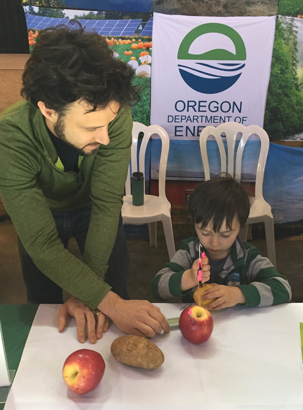 During an Earth Day event at the Oregon Garden in  Silverton , ODOE Engineer Blake Shelide showed a young boy how to create an electric current using fruits and vegetables.