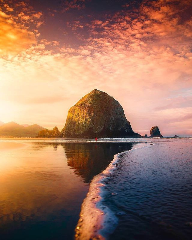 """@foxsbackpack and I made it to the famous Haystack Rock just minutes before this sunset popped off. Shot during our epic Pacific Northwest Road trip."" Have you ever run to a spot to catch the sunset? #BeautifulDestinations ( 📷: @lifewithelliott 📍: Cannon Beach, Oregon)"