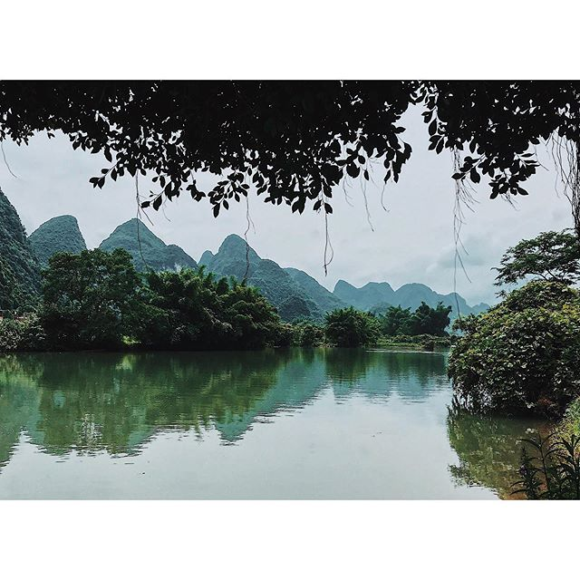 "Yulong River, Yangshuo, China (yep, genuinely China) . We found a 2002 copy of the @lonelyplanet in our hostel in Xingping near Yangshuo. Both towns were described as ""sleepy back-packer havens, just starting to feel the touch of Chinese development & tourism"" . Both towns are now mini-cities. With neon-strips, milk-shake bars & traffic jams. . We hired bikes & cycled along the paths of the Yulong to escape the hum. Fetching a breeze to cut thick humidity. Signs along the route read ""for the sake of your families, beware when swimming. The water is pretty deep."" . 'Pretty deep' is just deep enough to cool off. . . **keeping your mouth shut while swimming would have perhaps been better advice. We're adamant it made Steph sick - that or Chinese gutter oil 🤢... #realtravel . . . #china #yulongriver #yulong #anotherescape #authentictravel #placesoftheworld #wetravelgirls #damestravel #junglevibes #journeysofgirls #exploreoutdoors #travelphotography📷 #travelwithpurpose #travelstories #experientialtravel #adventuretravels #intrepidtravel #naturegreen #naturecapture #cntraveller #anotherescape #getlostnow #lonelyplanet"