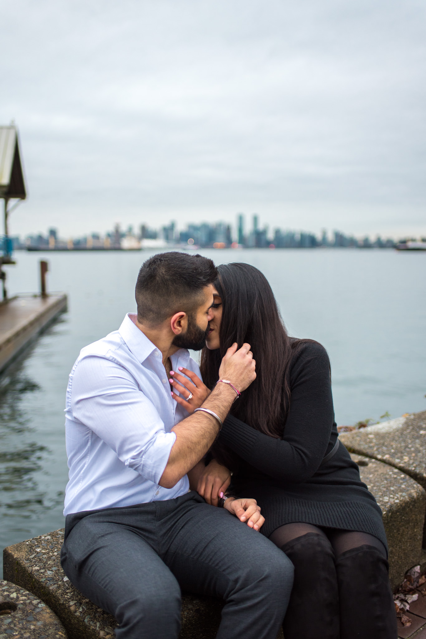 An engaged couple shares a kiss in North Vancouver BC