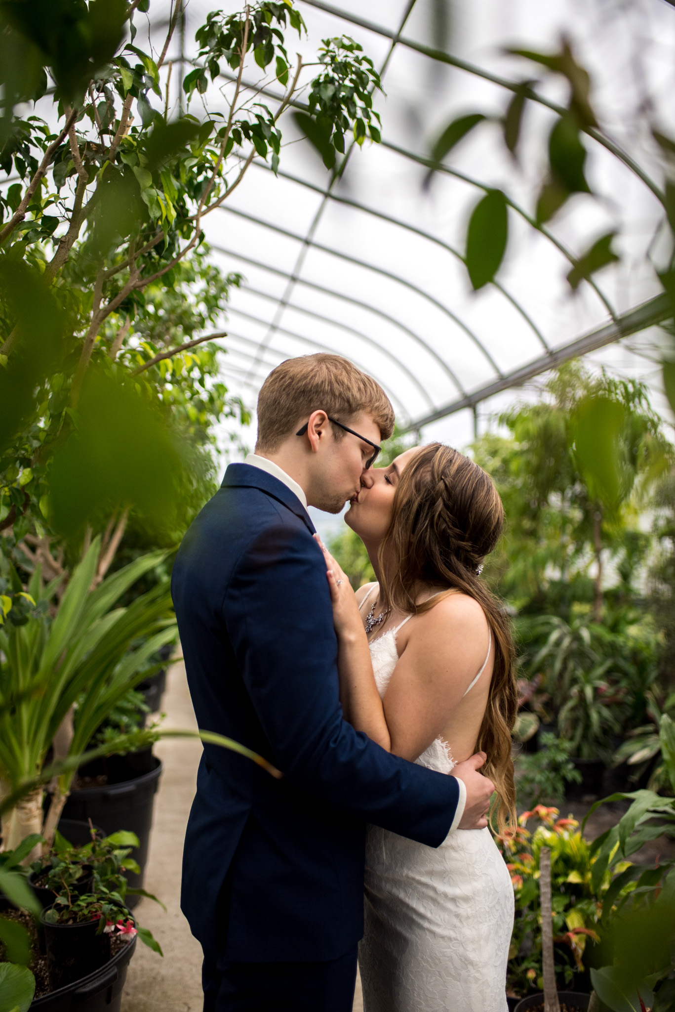 Bride and groom kissing in a greenhouse at Woodbridge Ponds
