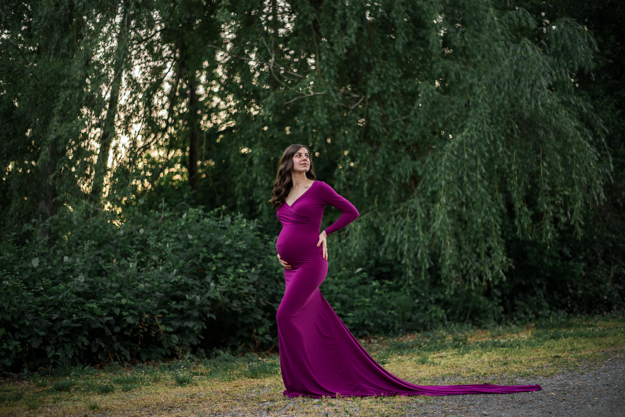 Pregnant woman standing in front of a tree in a park in Burnaby BC