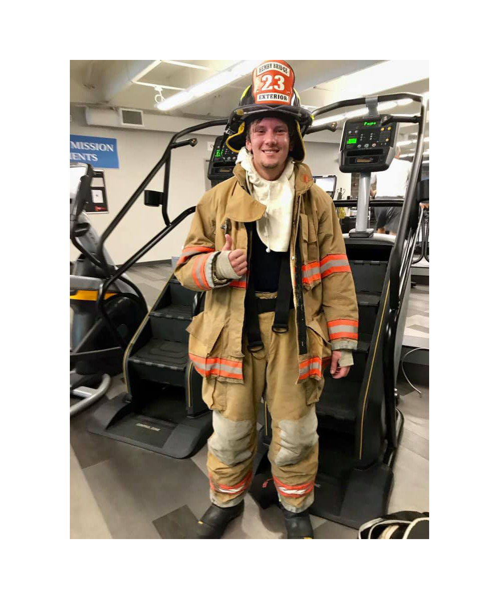 News Around Town: In honor of September 11, Hemby Bridge firefighter Tyler Kaul took to the Brace YMCA Stairmaster. Kaul dressed in full turnout gear to climb 120 floors, representing the number of stories climbed by emergency responders in NYC on 9/11. - Image via Brace YMCA Facebook