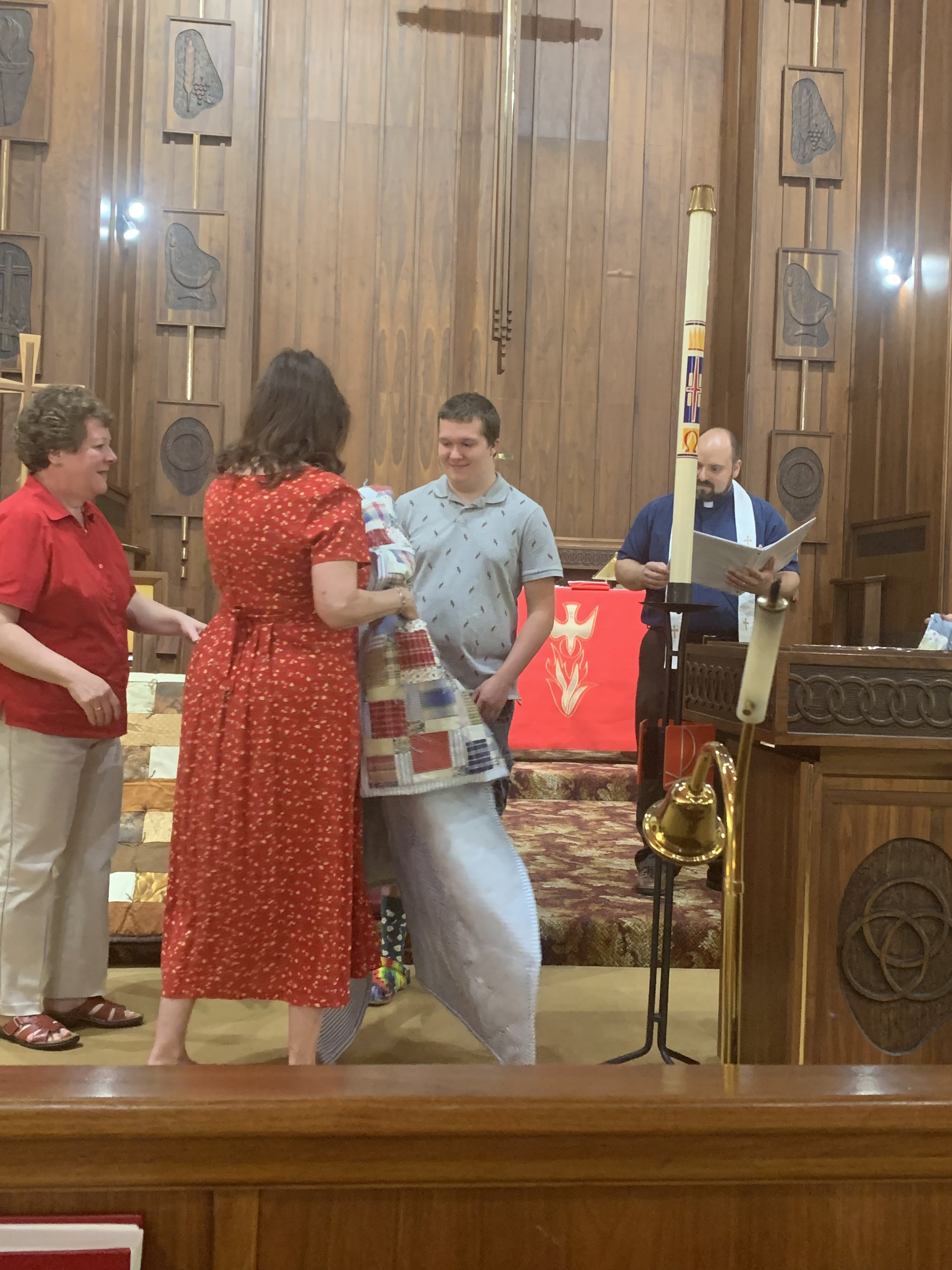 The Quilters of Hope presenting quilts to two of the Good Hope/Zion Lutheran Ministry high school seniors. (photo by Susie Hlawati)