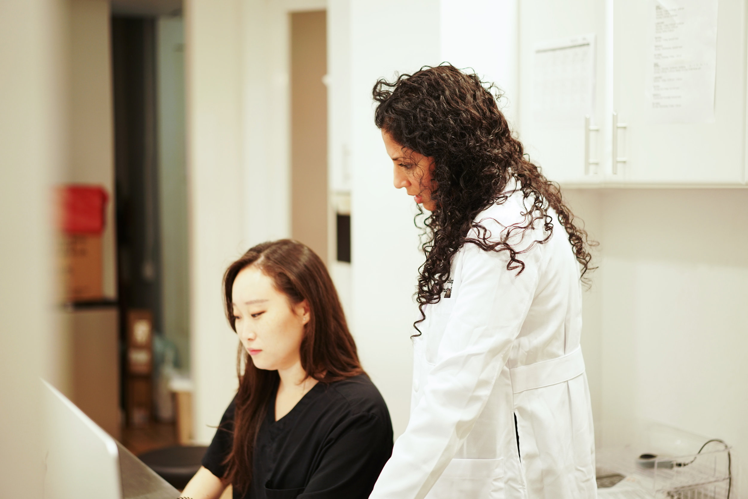 Image of a doctor in an office standing up next to an assistant who's sitting down next to her