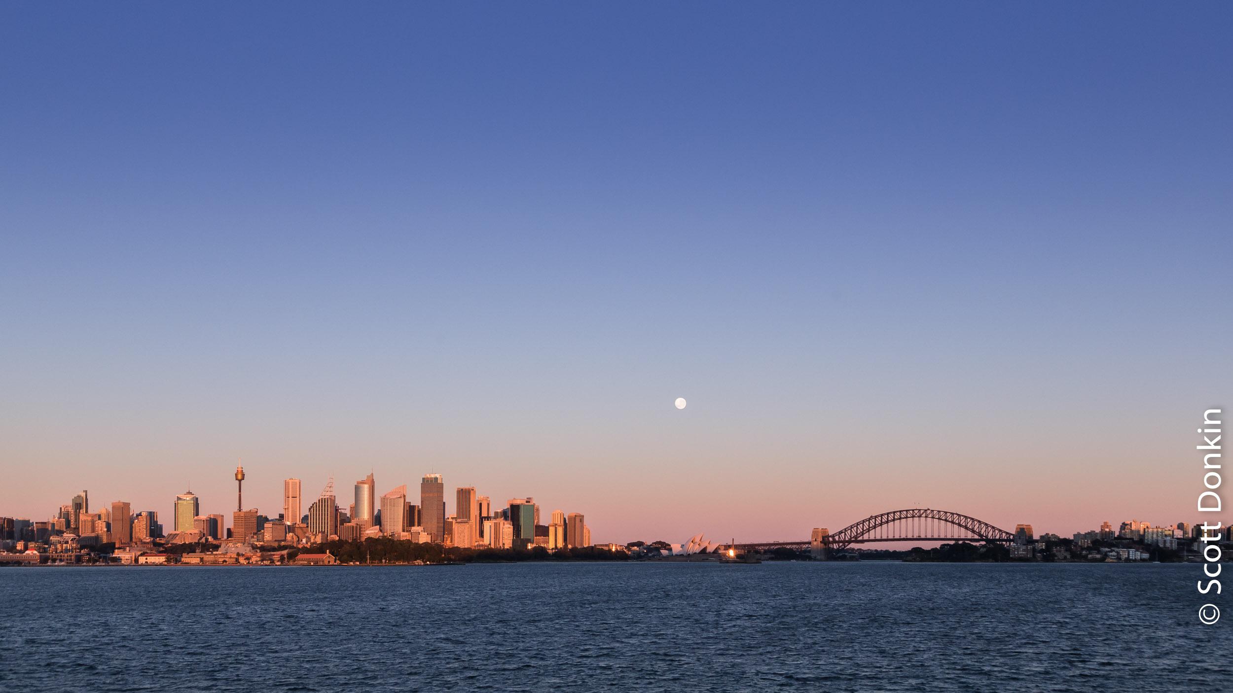 Moonset over Sydney Harbour, city skyline and Sydney Harbour Bridge. Sunrise, 9 August 2017.