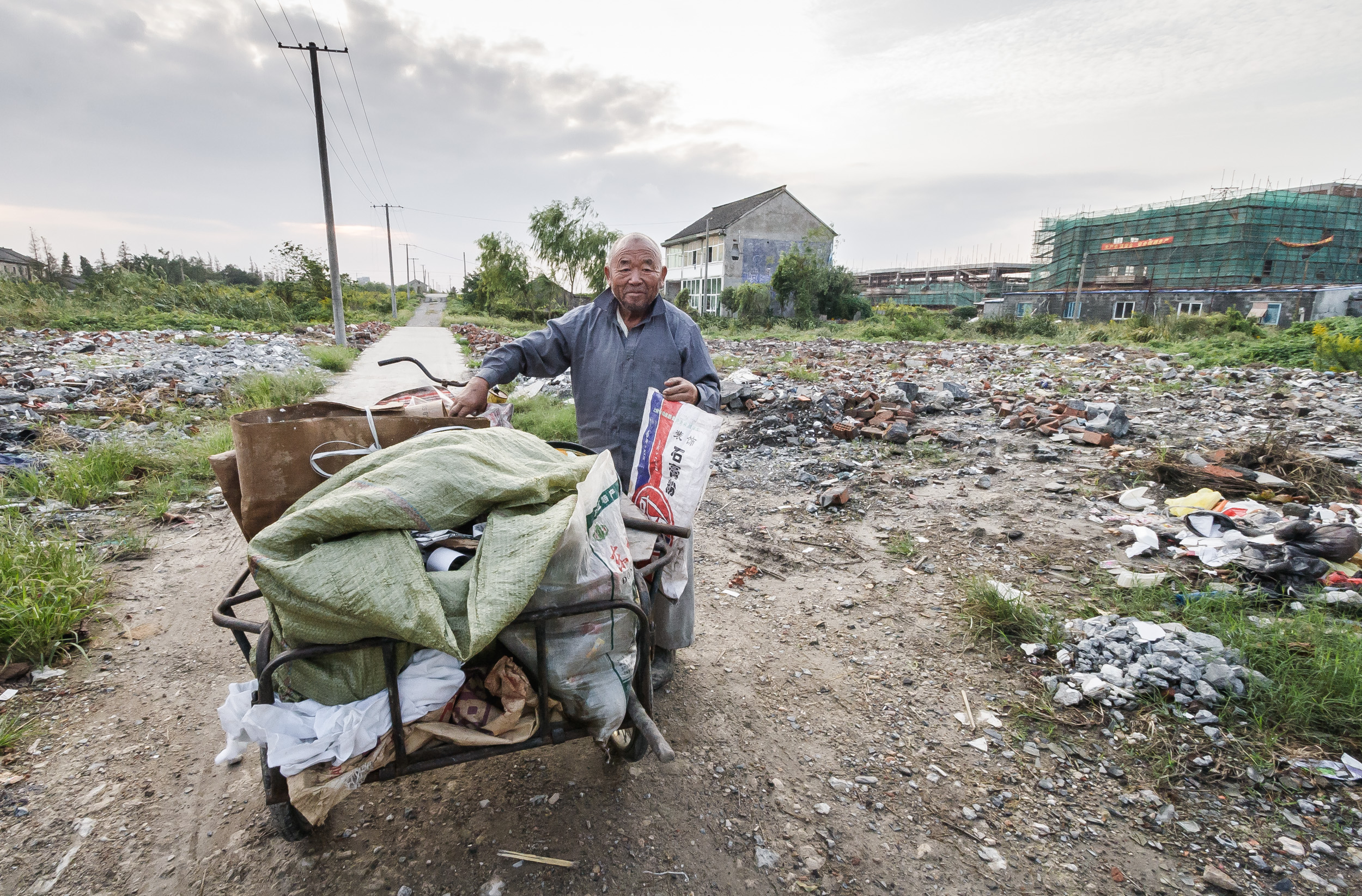 A man with a barrow collects recyclable material in a former housing area. Shanghai, China.