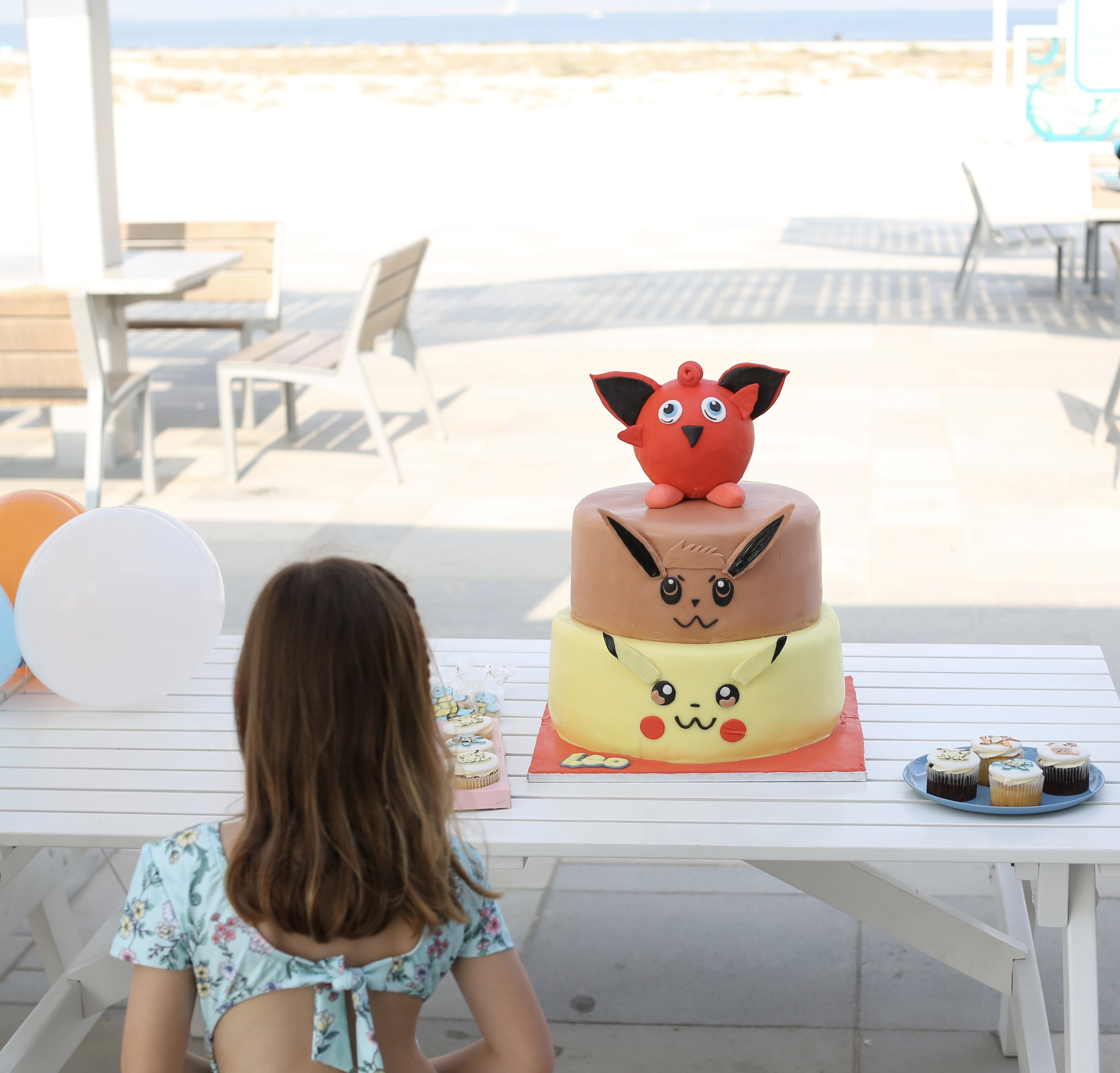 Just a girl standing in front of her three-tier Pokémon cake