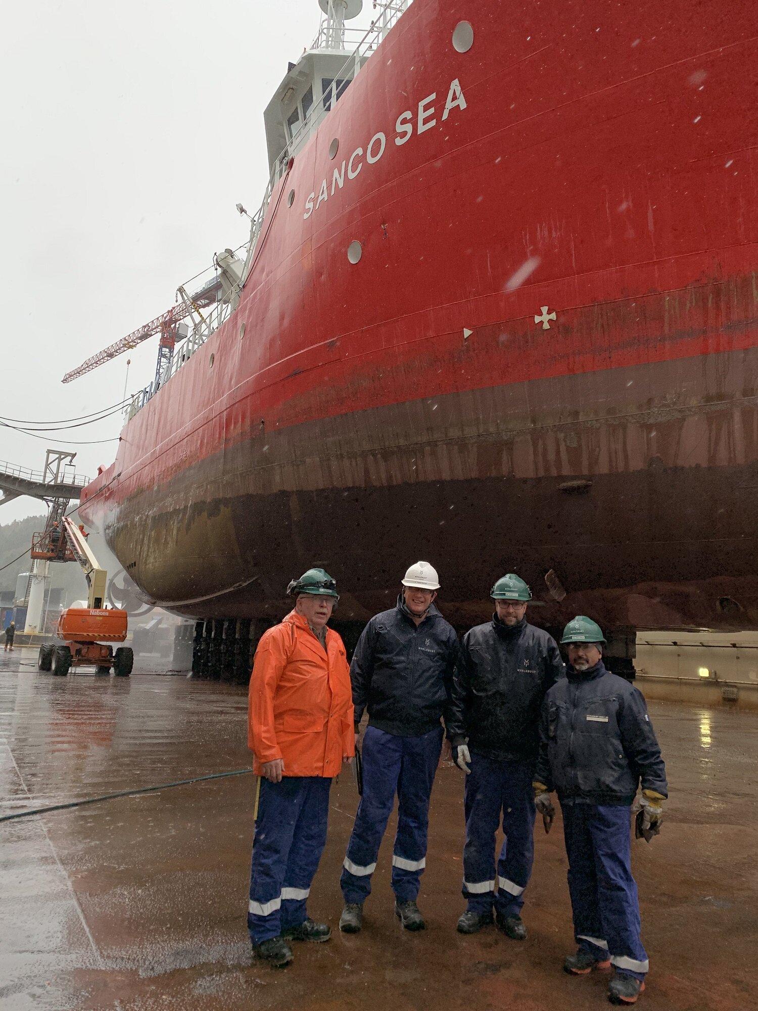 Framfor det flotte skipet «Sanco Sea» i dokka: Ove Paul Olsen (HVO), Torben Sandvik (HMS), Torgeir Hjelle (VO) og Stan Valeriu (VO).