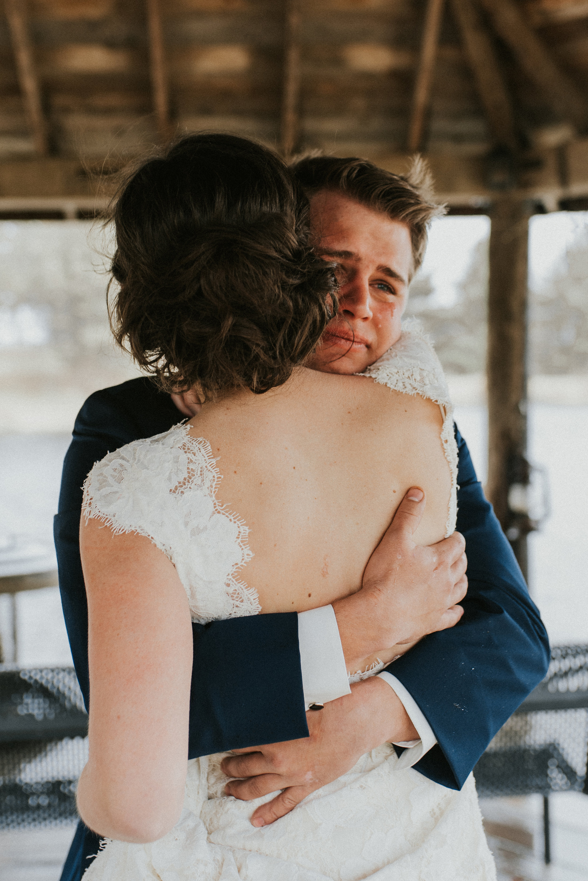 Emotional first look with groom crying and hugging bride - this was a rainy April wedding in West Branch, Iowa | Photo by Marissa Kelly Photography