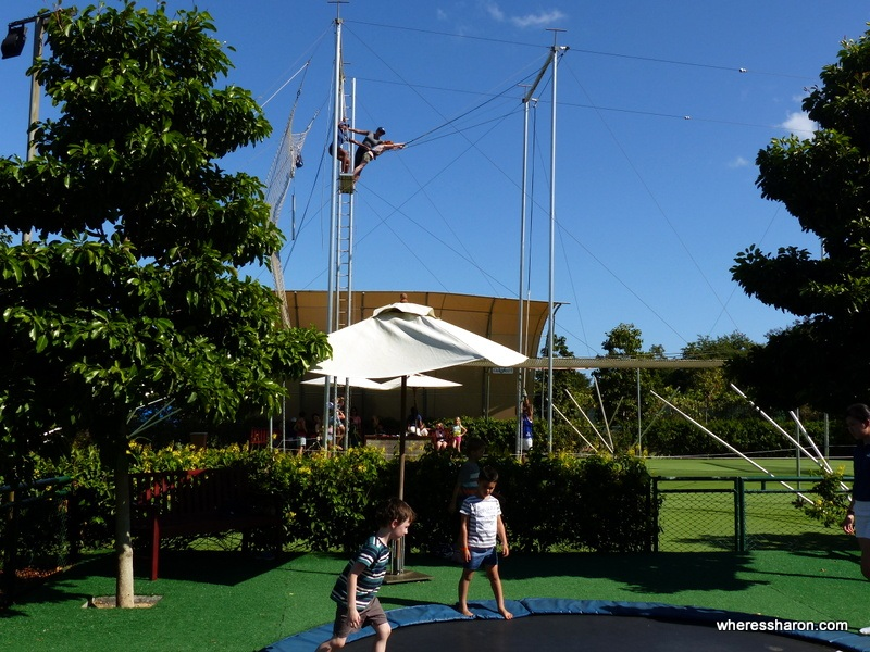 S flying through the air on a trapeze while Z jumps on the trampoline. All part of a day in Mini Club!
