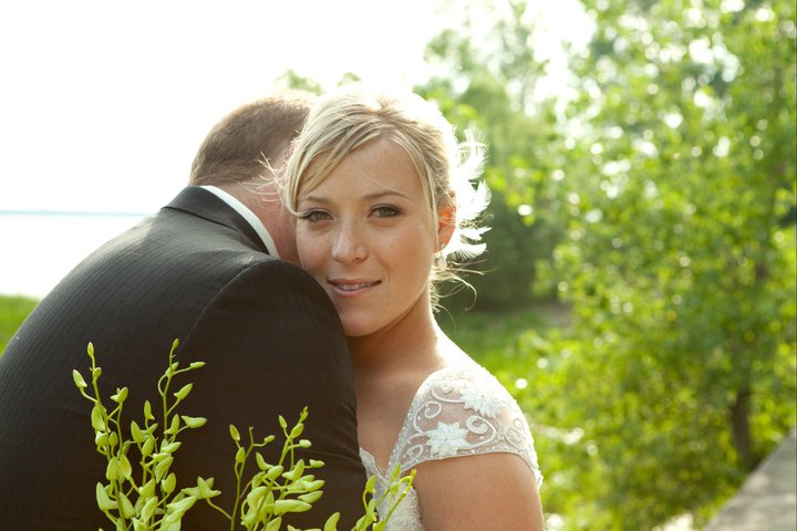 Woman in wedding dress hugging her husband looking at the camera