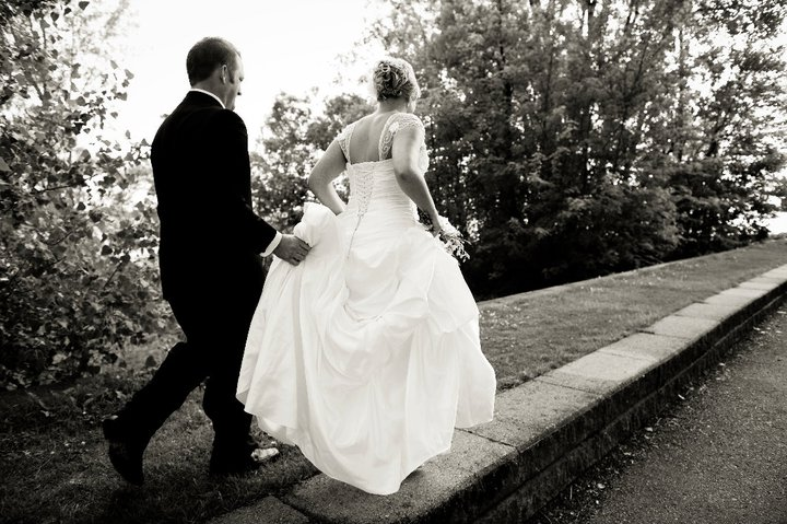 black and white image of a bride and broom running