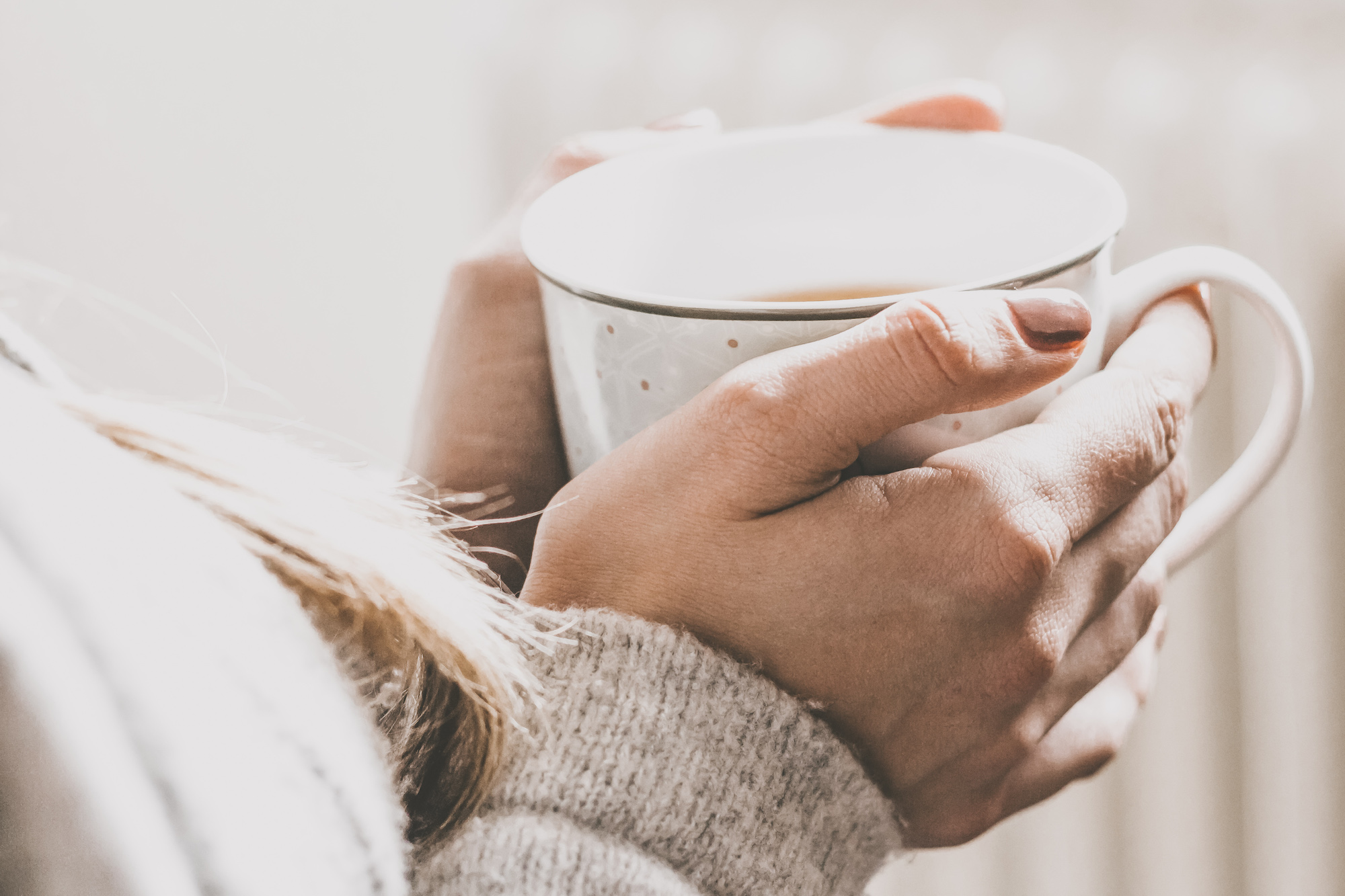 Junge Frau wärmt Hände an Teetasse
