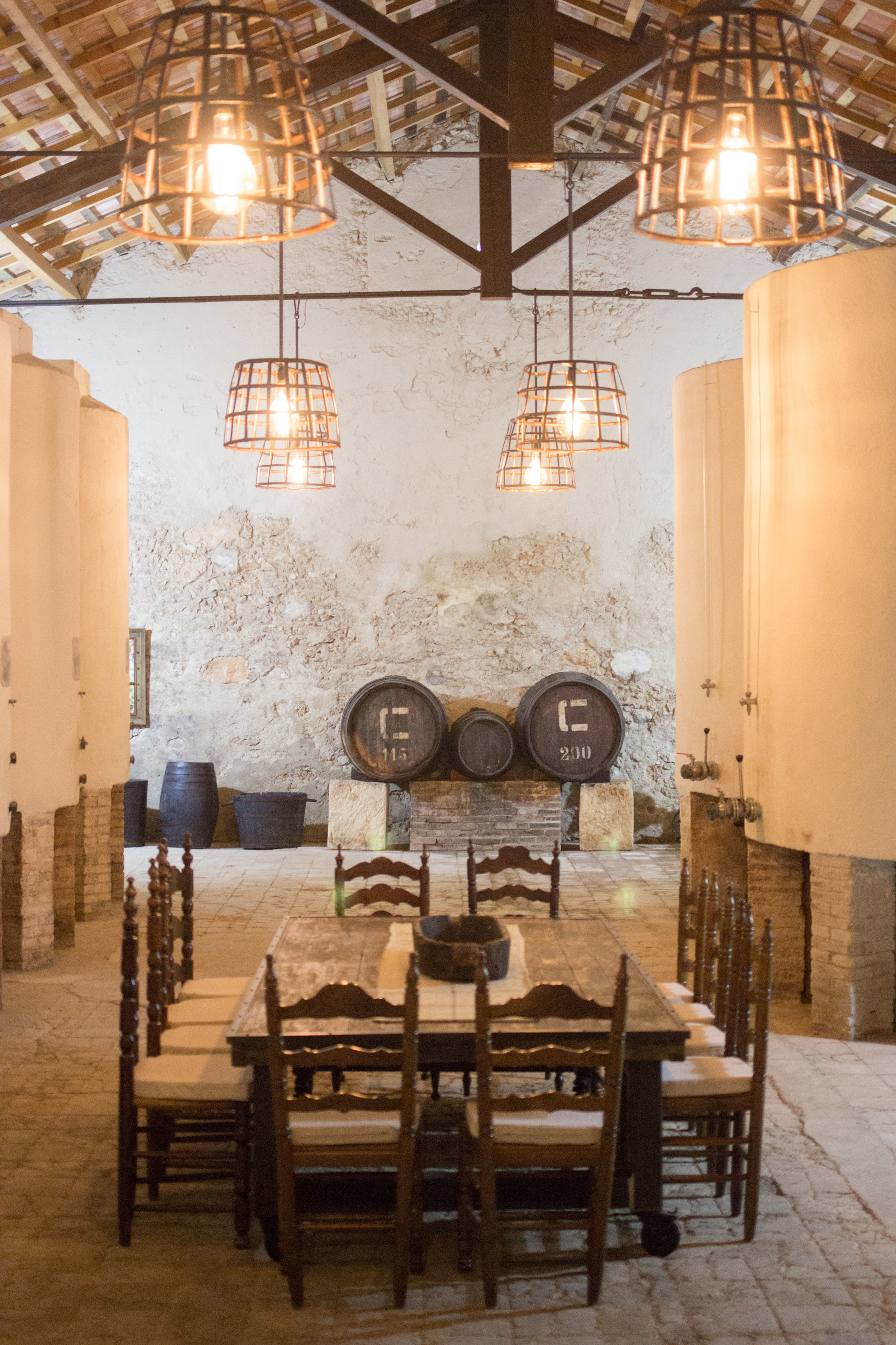 Design light fixtures, high ceiling, large cool space with a handmade upcycled table in the middle and vintage wine barrels in the background