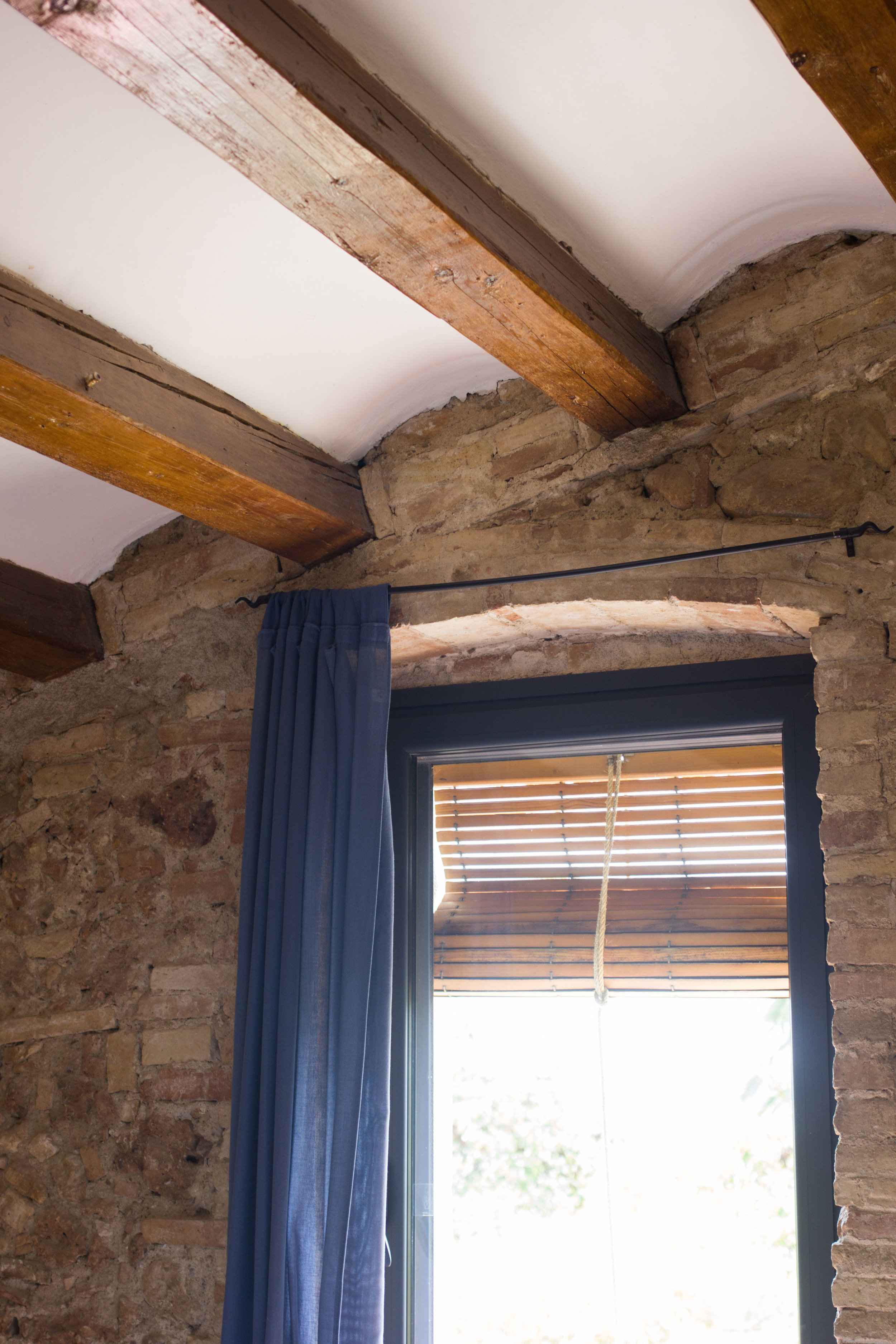 Wooden beam ceiling interior design with blinds on the curved window
