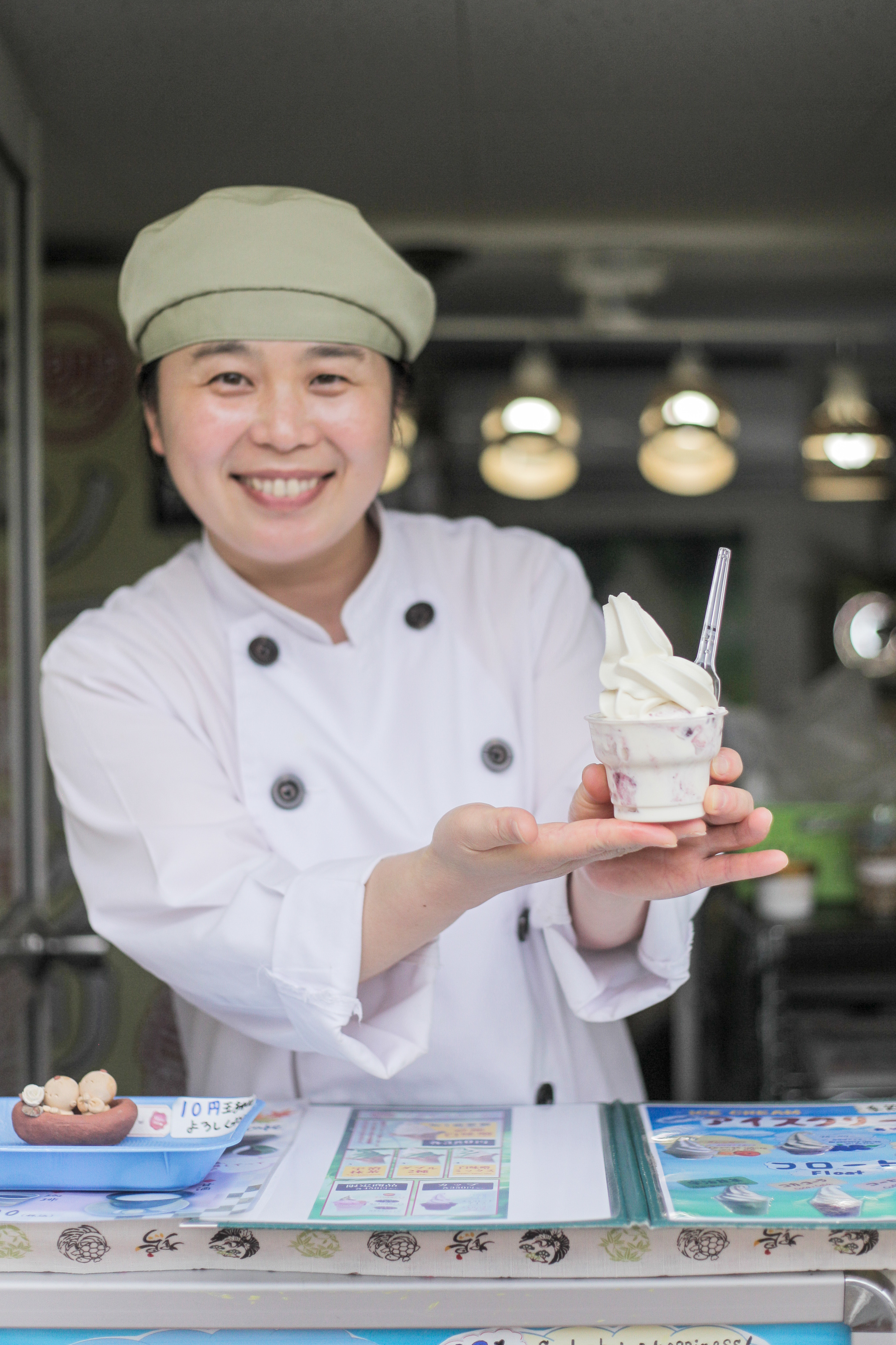 Hana-san of Hana Ice showing off her blueberry ice cream topped with white miso soft serve (¥380).