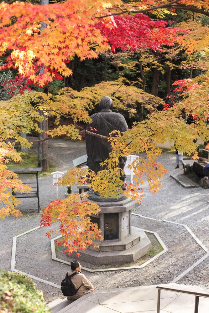Kobo Daishi's statue stands amid autumn colours at the Imakumano Kannon Temple