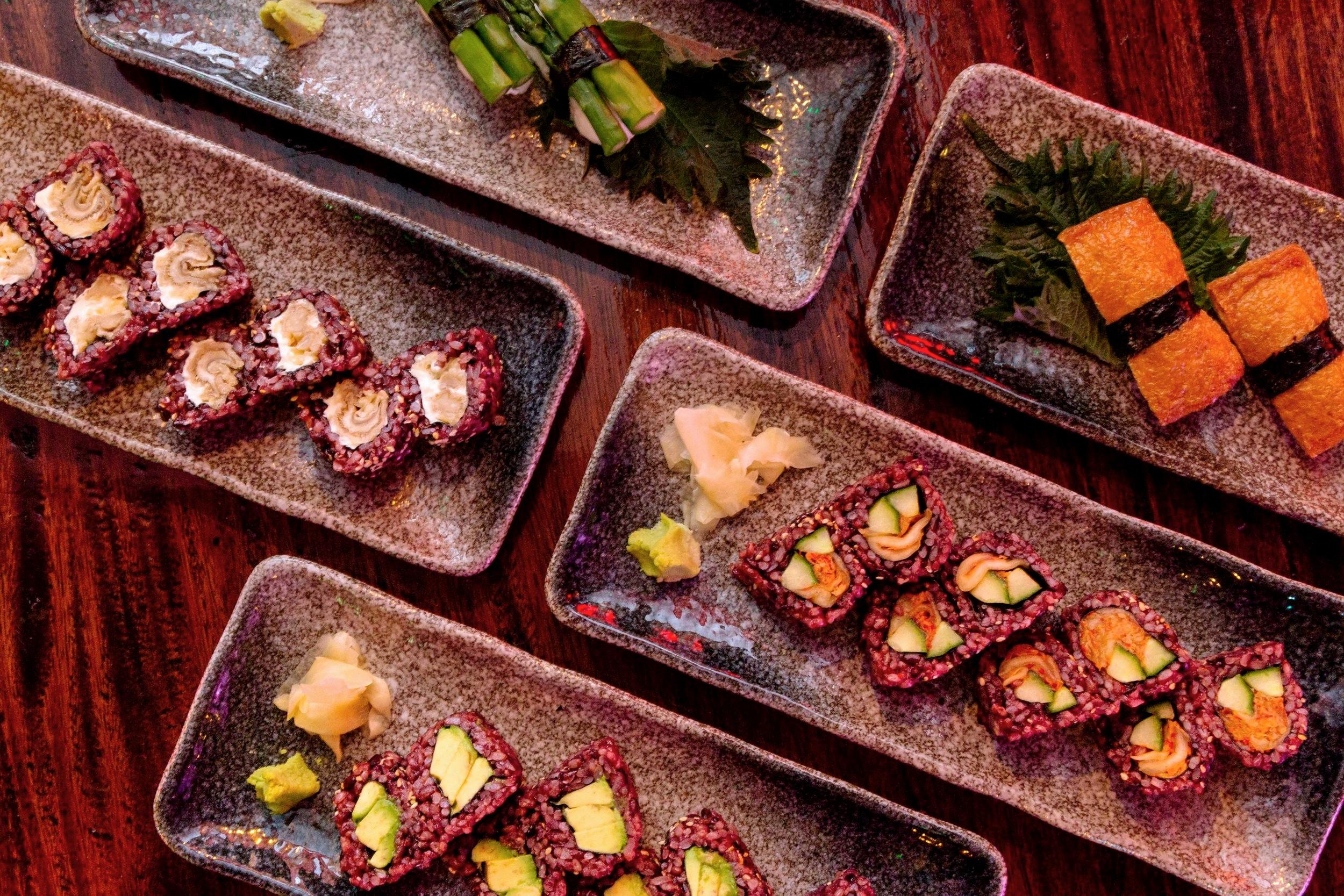 Clockwise from top left: Asparagus nigiri with white rice; Inari nigiri; Cucumber and Kimchi norimaki, Avocado norimaki, and Oyster Mushroom and Cream Cheese norimaki [vegan option available without cream cheese], all with black rice option
