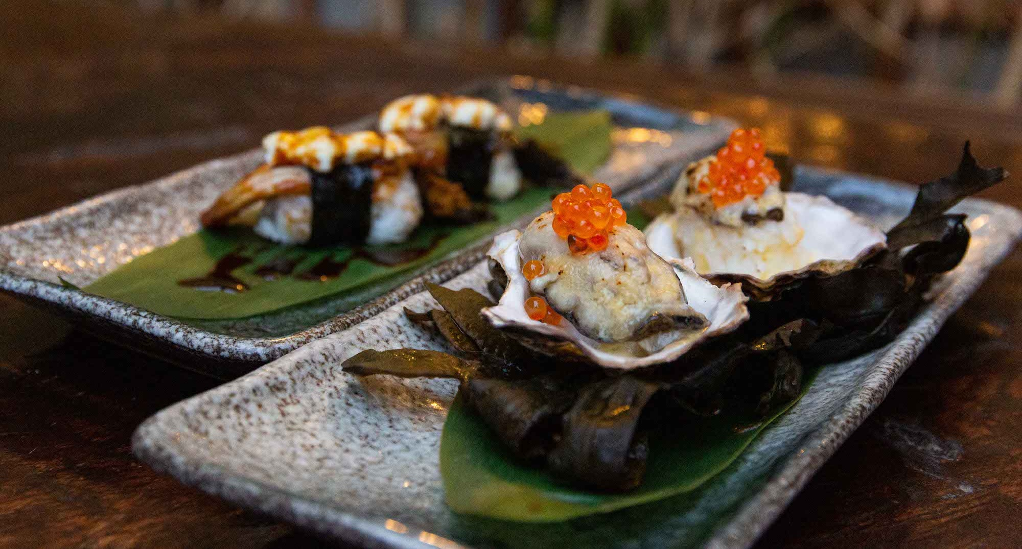 Grilled eel nigiri with torched goat's cheese (back), and Grilled Oysters with Masago over Irish Seaweed and Banana Leaf