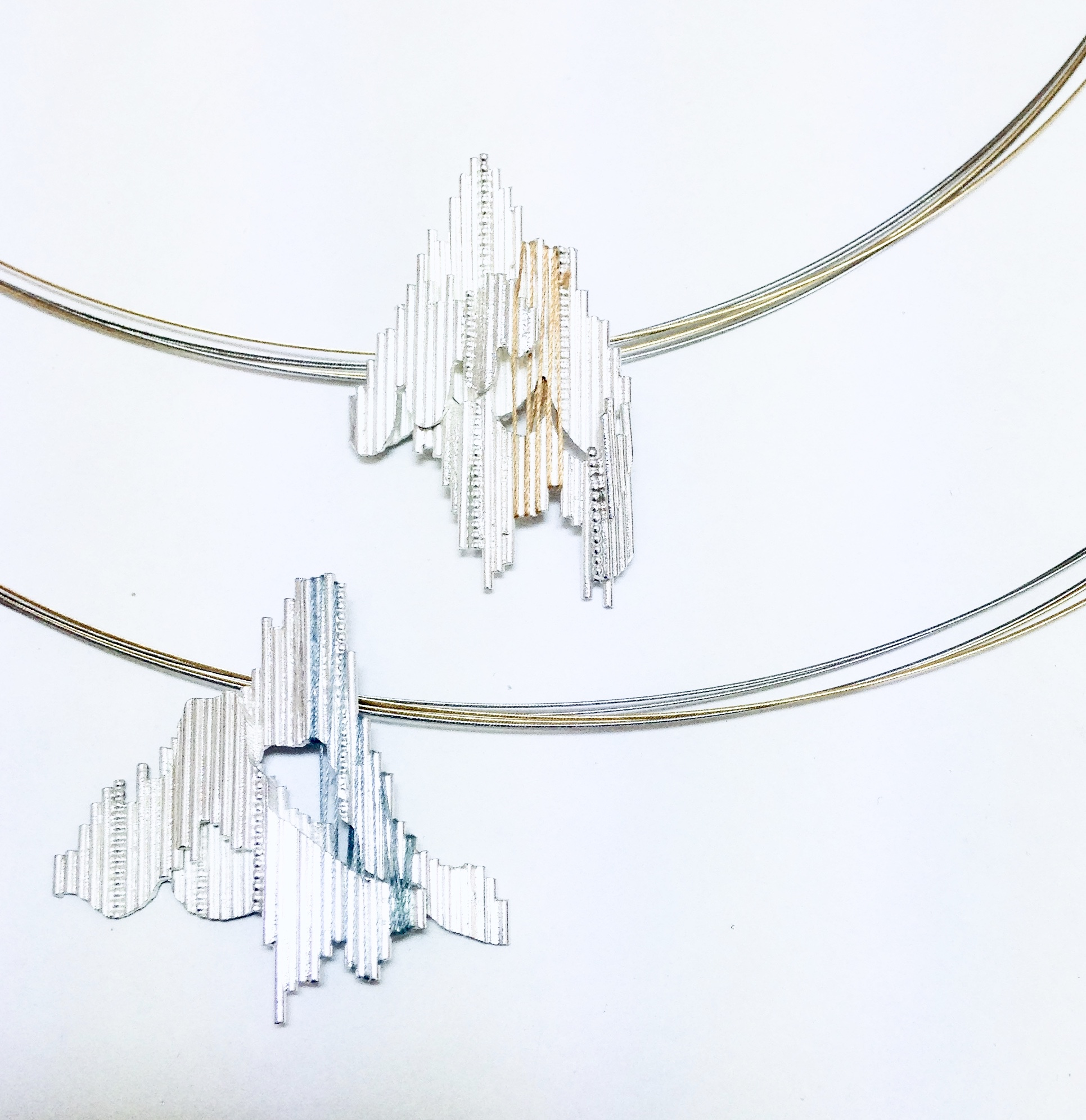"""Follow the Thread - Necklaces made for the Dazzle exhibition, """"Follow the Thread"""". Exhibition at the Dovecot Studios Edinburgh, 2013.Two Silver necklaces, with silk threads, steel neck wire with 18ct Gold Plating. The design depicts a fragmented landscape, with threads weaving through the linear structure to highlight the depth of form."""