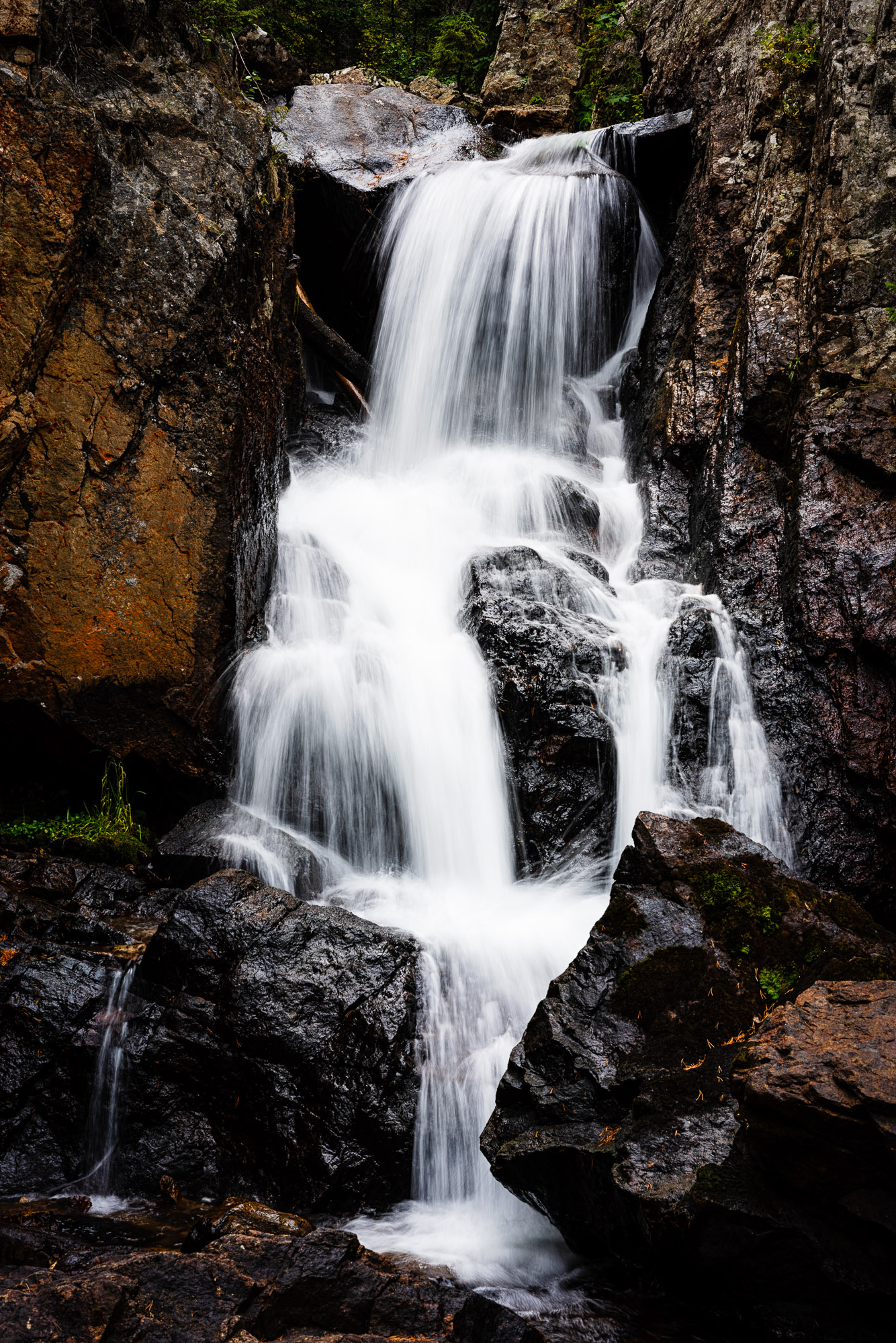 - color edit of waterfall in indian peaks wilderness with much higher contrast - notice the rocks are much darker with some shadows now lacking definition and the water is a bit lighter - losing some of its definition