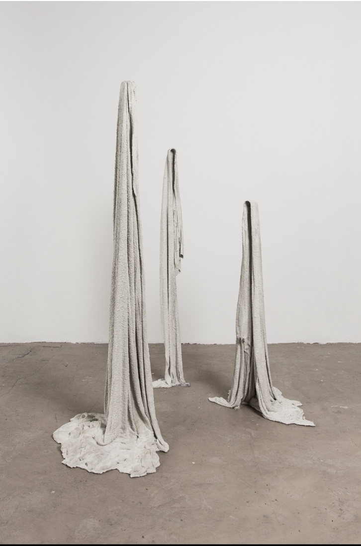 "Three towels on floor, 2019.  Concrete, cotton toweling. 56 x 23 x 20"". 