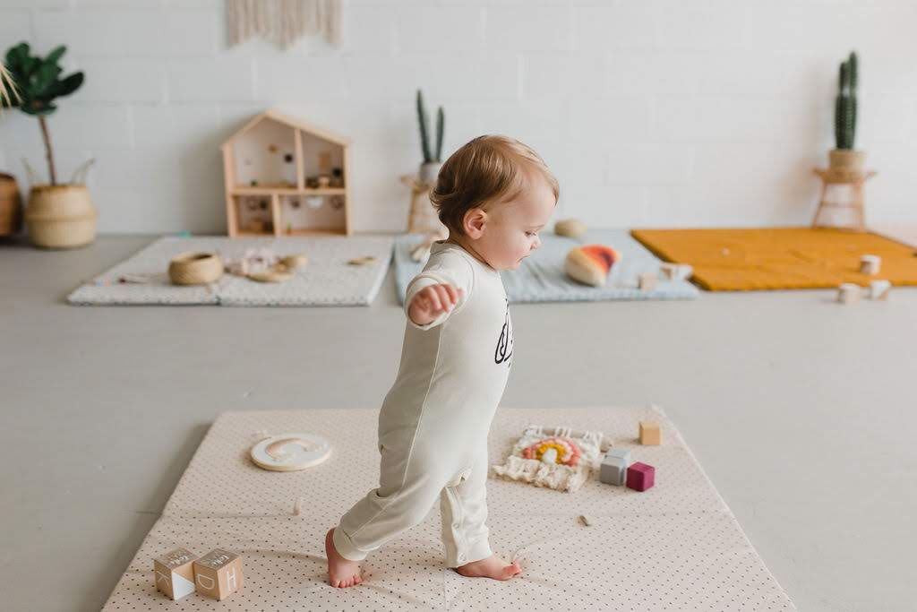 baby walking on play mat in natural light studio