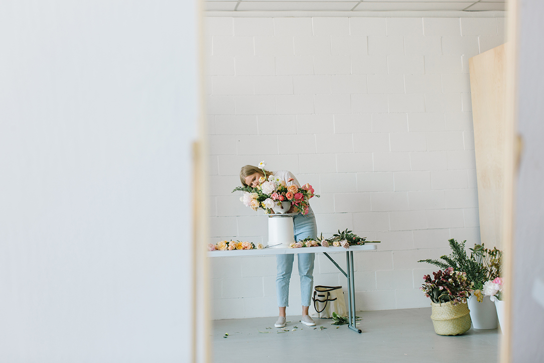 florist arranging flowers on table reflected through mirror in white rentable studio in danville ca.jpg