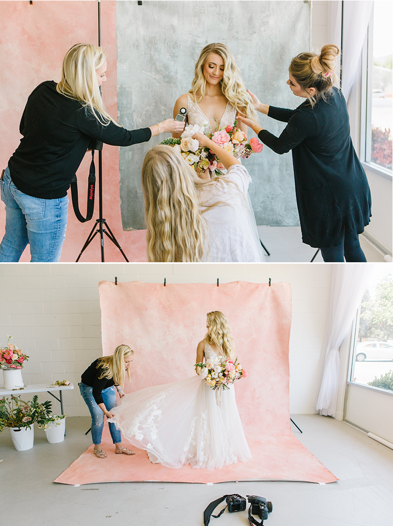 photographer and makeup artist prepping bridal model for photoshoot in front of a pink custom painted backdrop in a natural light studio in pleasanton ca.jpg