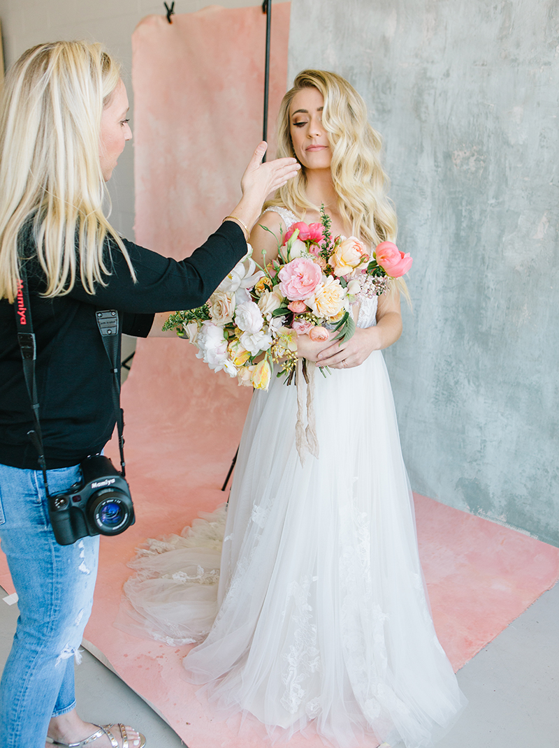 portrait photographer directing bridal model in front of a pink custom painted backdrop in a natural light studio in livermore ca.jpg