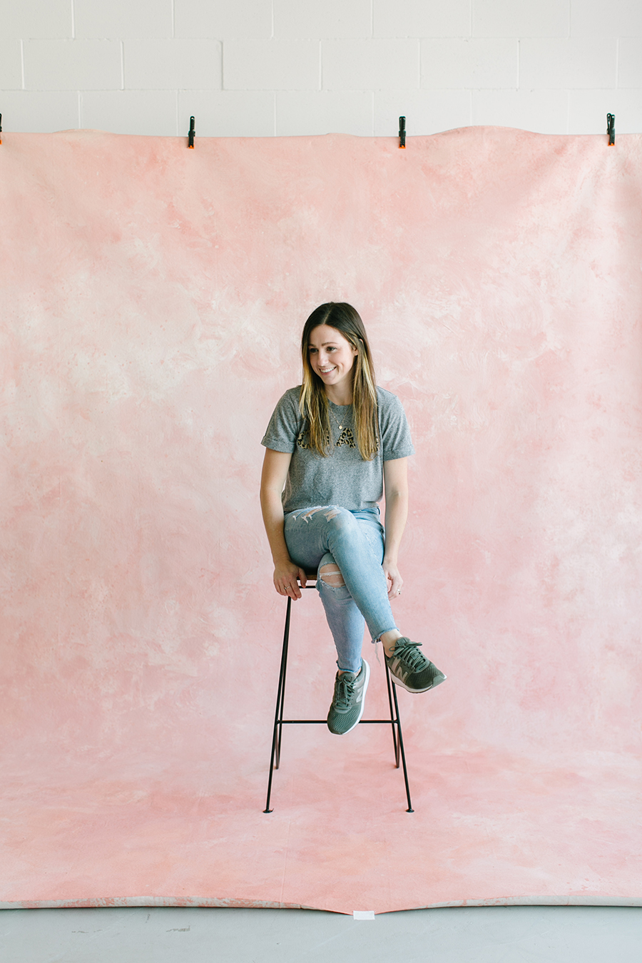 painter sitting on wooden stool in front of pink custom painted backdrop in natural light studio in dublin ca.jpg