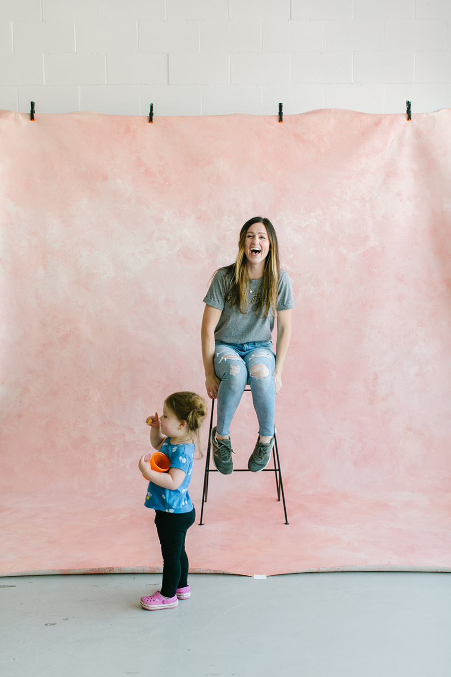 painter sitting on wooden stool in front of pink custom painted backdrop with little girl.jpg