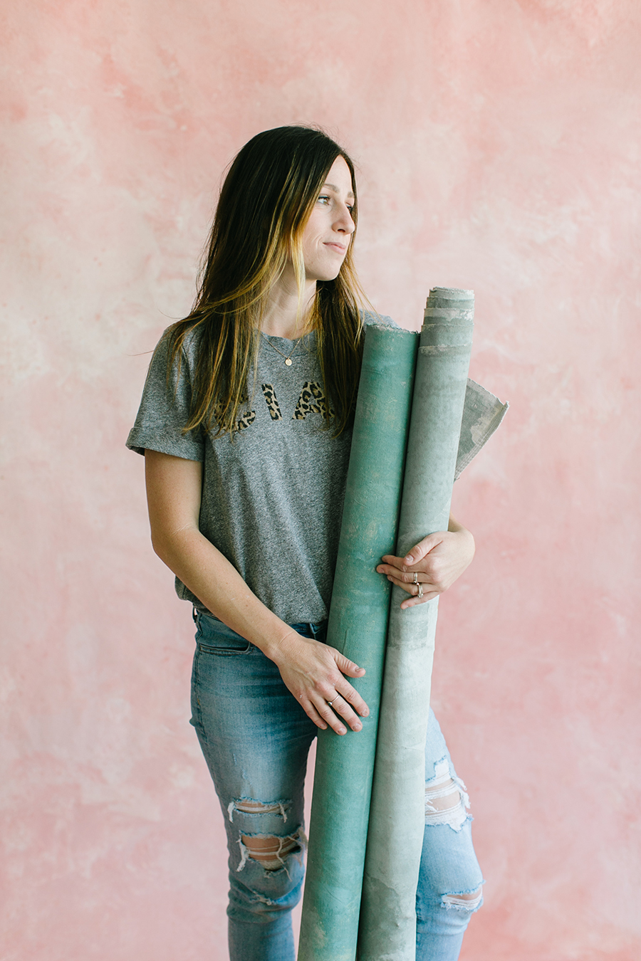 painter standng in front of pink custom painted backrop holding grey rolled backdrops in rentable white studio in pleasanton ca.jpg