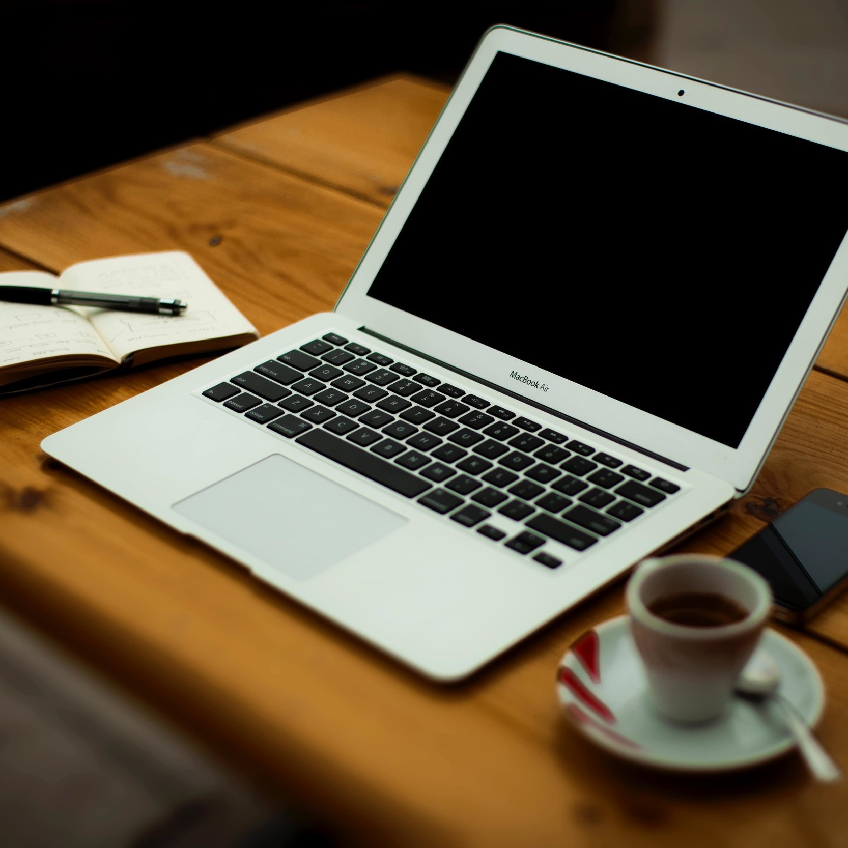 MacBook laptop with black screen and a notebook beside it.